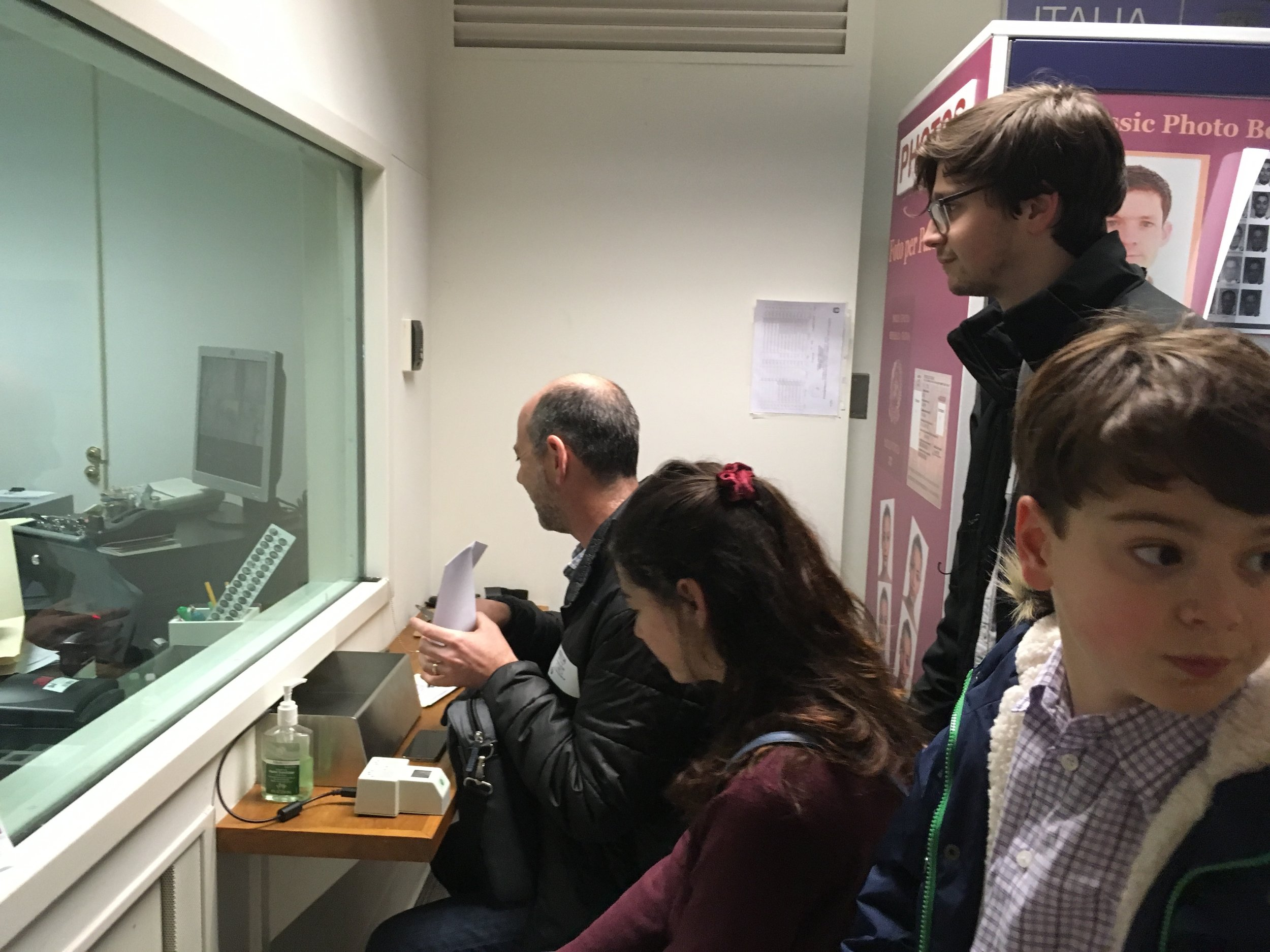 Our visit last week, with the plexiglass and the little drawer to shuttle documents back and forth. Unlike last time, this time there was much shuttling.