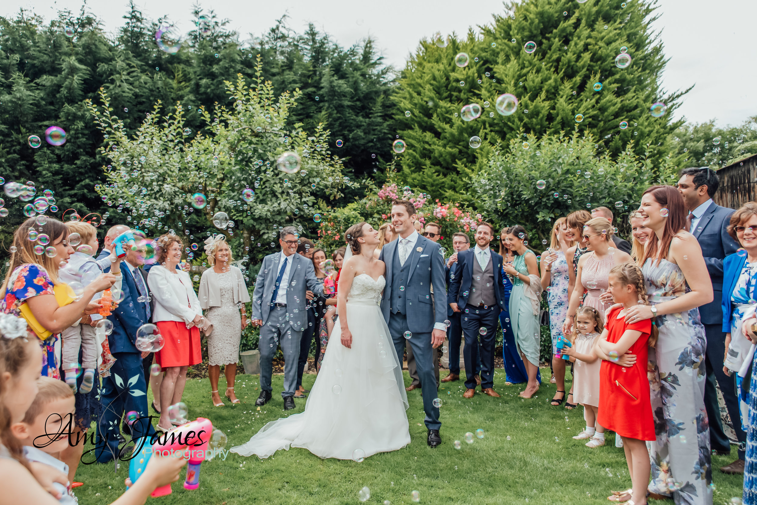 Taplins Place Wedding - Bride and Groom with bubbles instead of confetti - Amy James Photography - Hampshire Wedding Photographer