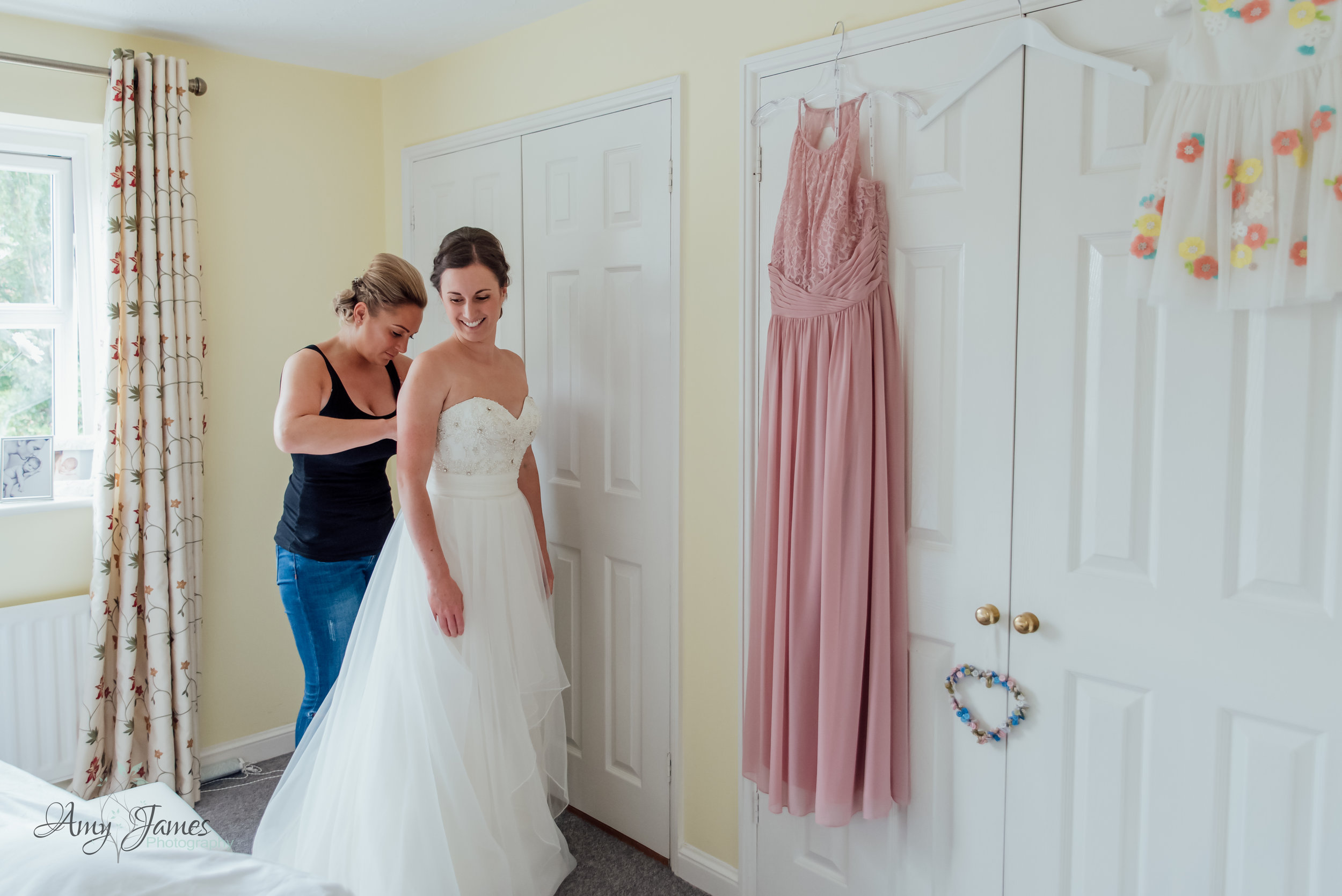 Brides sister helping her into her wedding dress - Amy James Photography - Taplins Place Wedding - Wedding photographer Hampshire