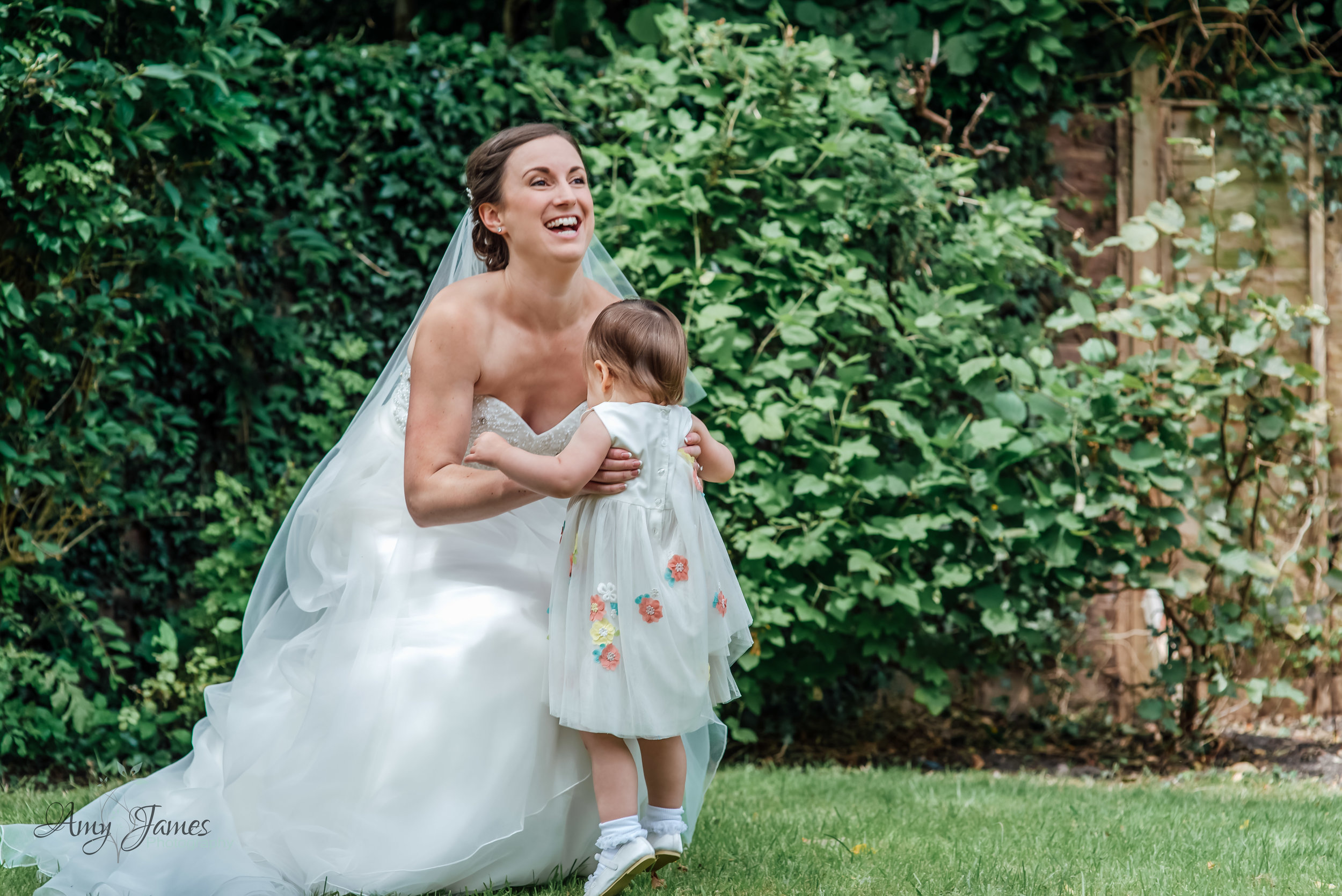 Bride throwing flower girl into the air