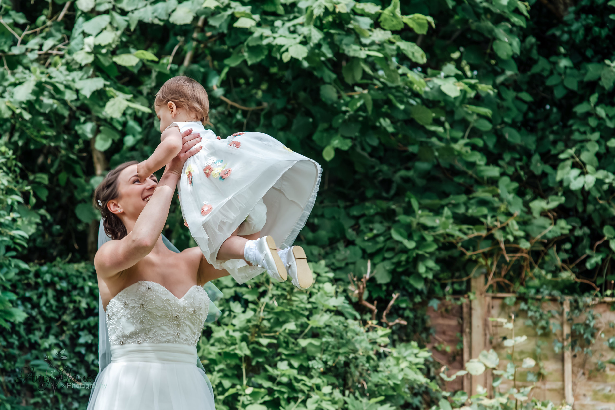 Bride throwing flower girl into the air - Amy James Photography - Wedding photographer Hampshire - Taplins Place Wedding