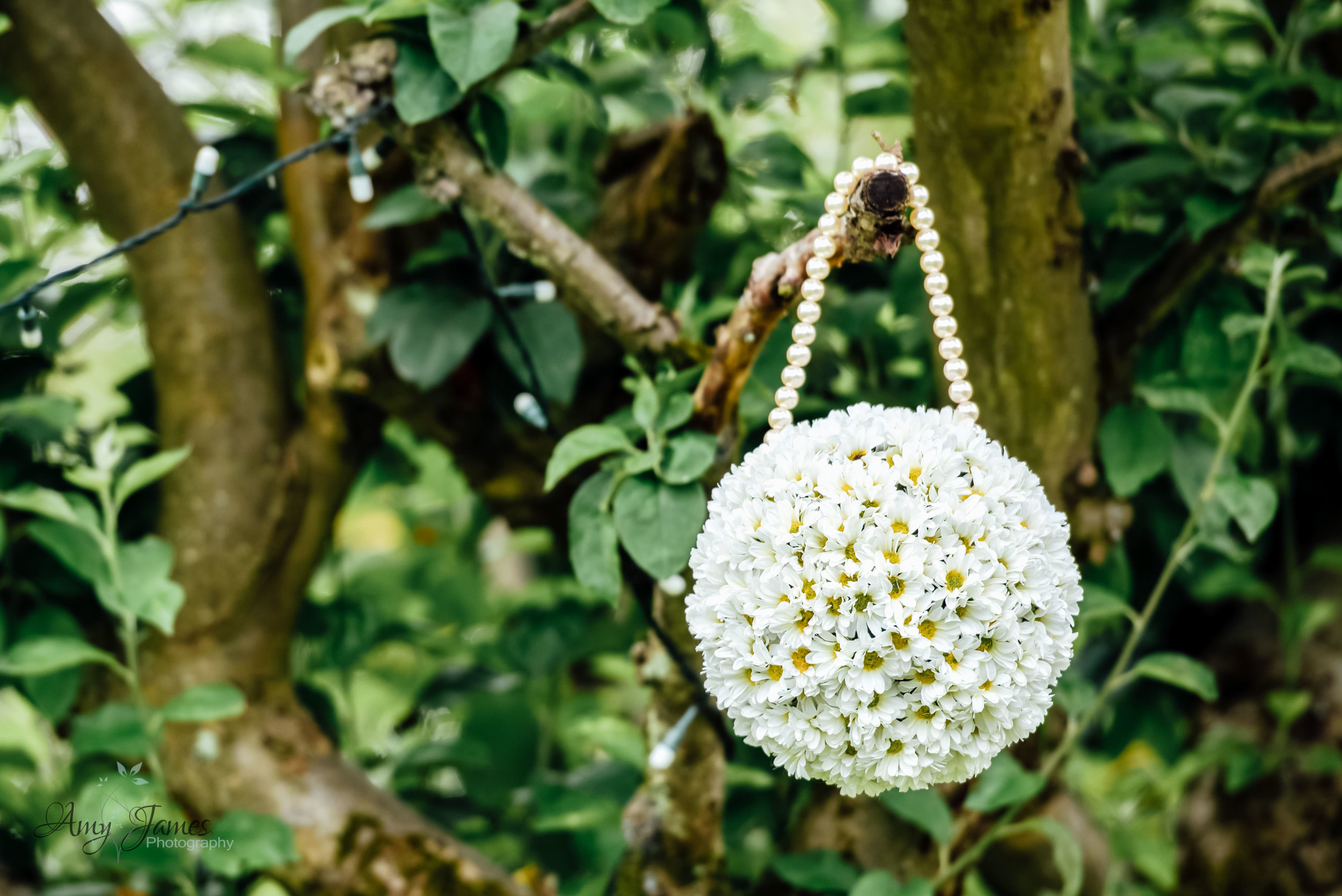 Flower ball in tree at an outdoor wedding ceremony - Amy James Photography