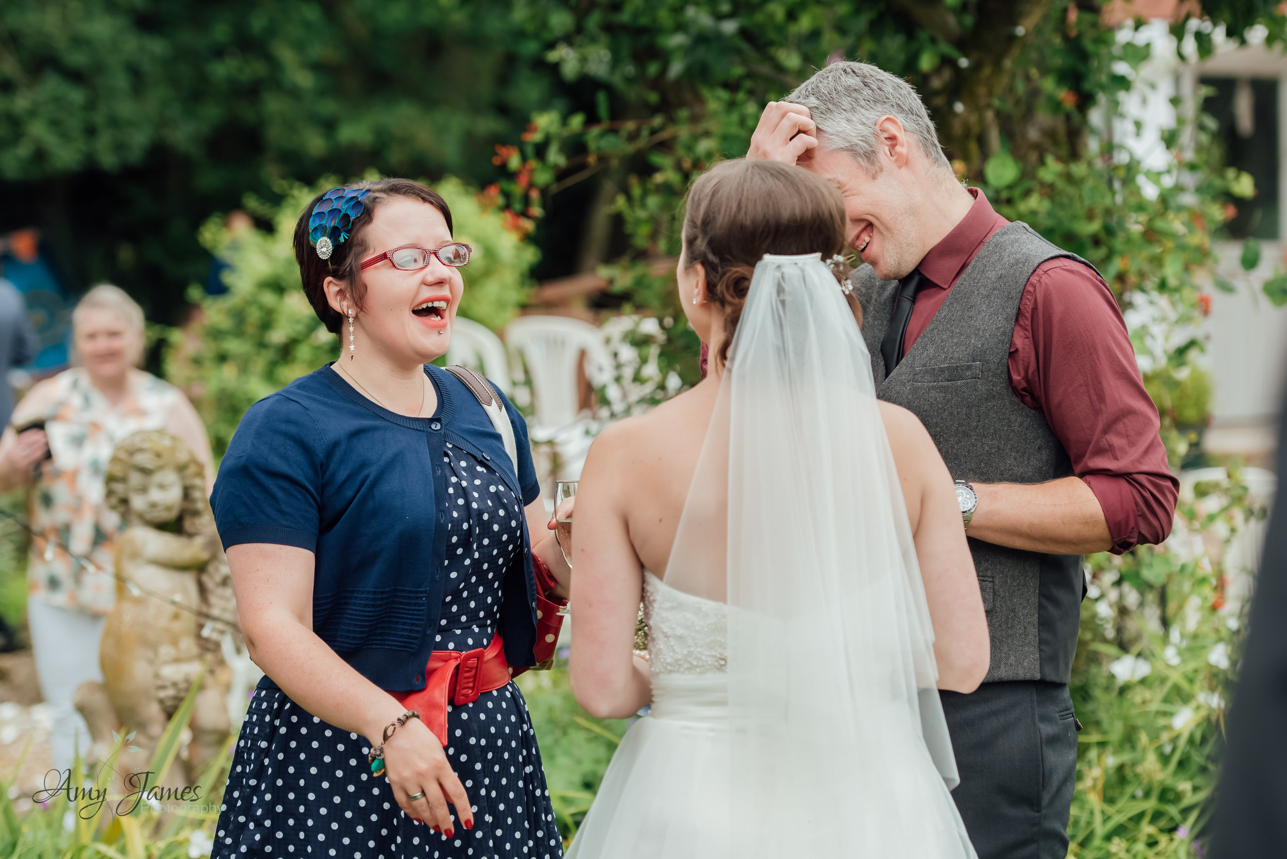 guest laughing at outdoor wedding ceremony by Amy James Photography Hampshire wedding photographer at Taplins Place