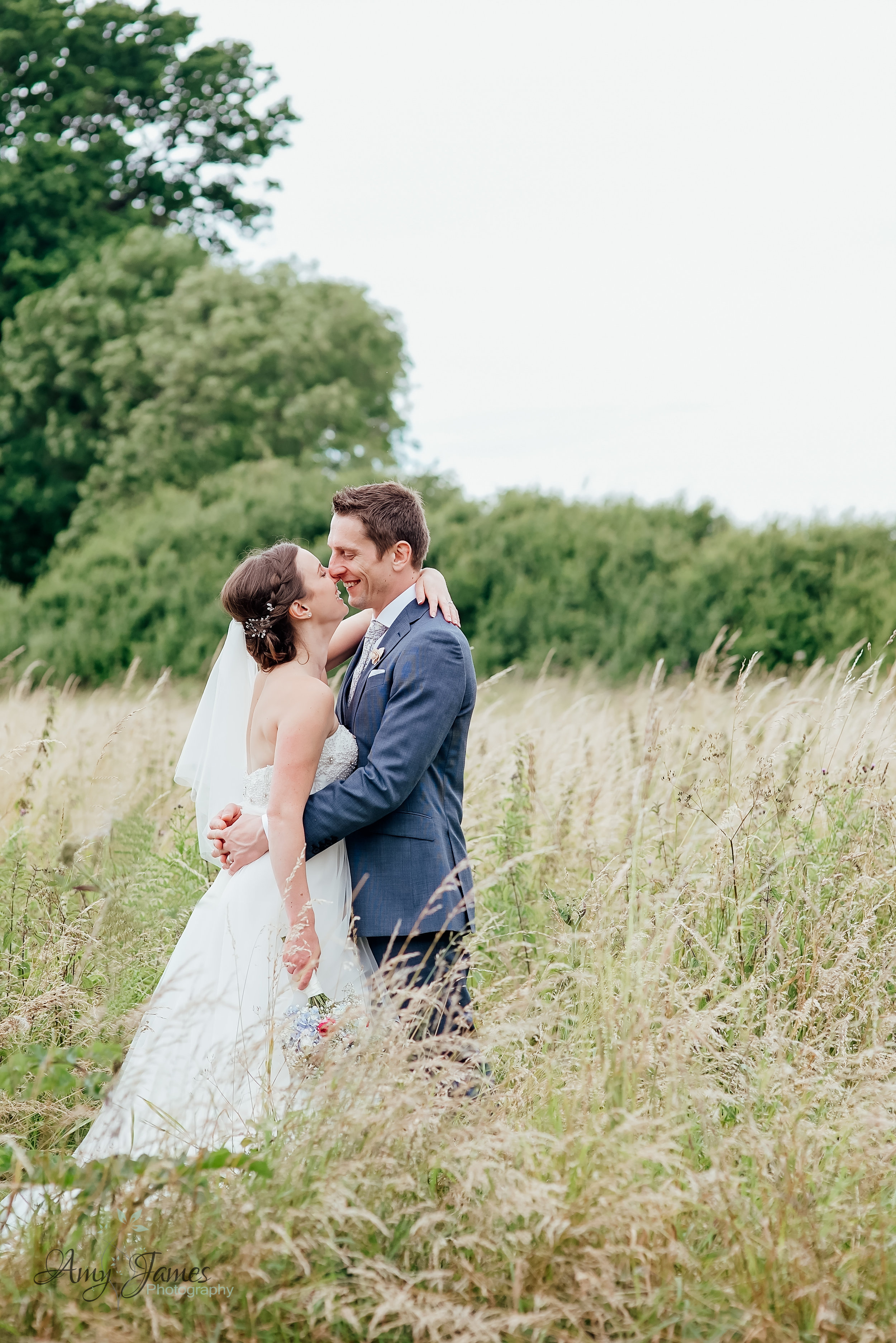 Bride and Groom in field at outdoor wedding venue Hampshire by Amy James Photography Hampshire Wedding Photographer - Taplins Place Wedding