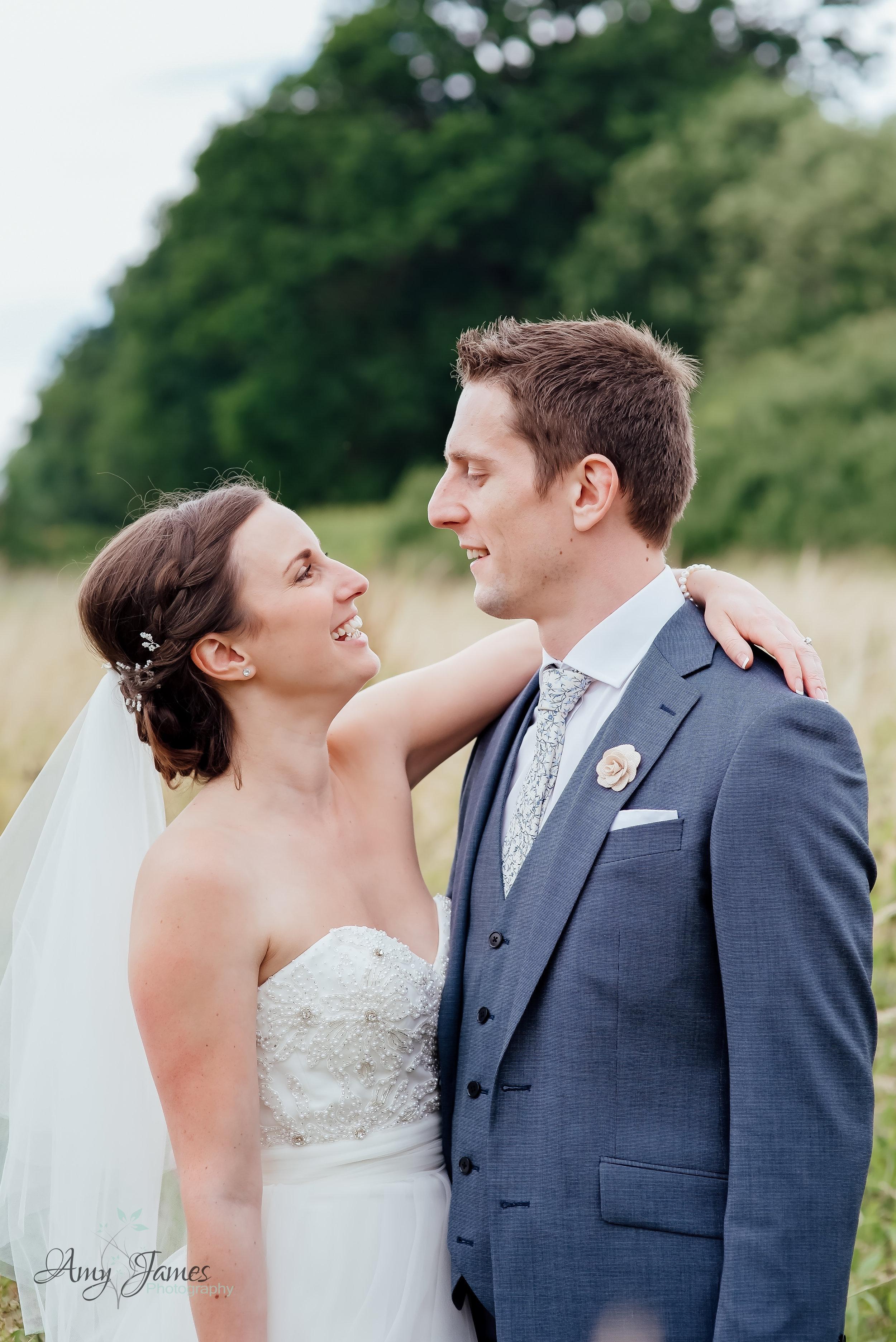 Bride and Groom in field at outside wedding venue Hampshire Taplins Place by Amy James Photography