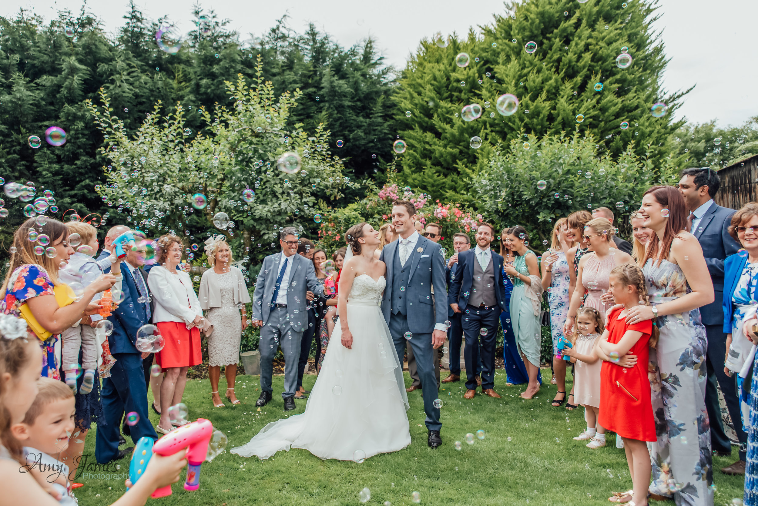 Bubble confetti at outdoor wedding venue Hampshire - by Amy James Photography Hampshire Wedding Photographer