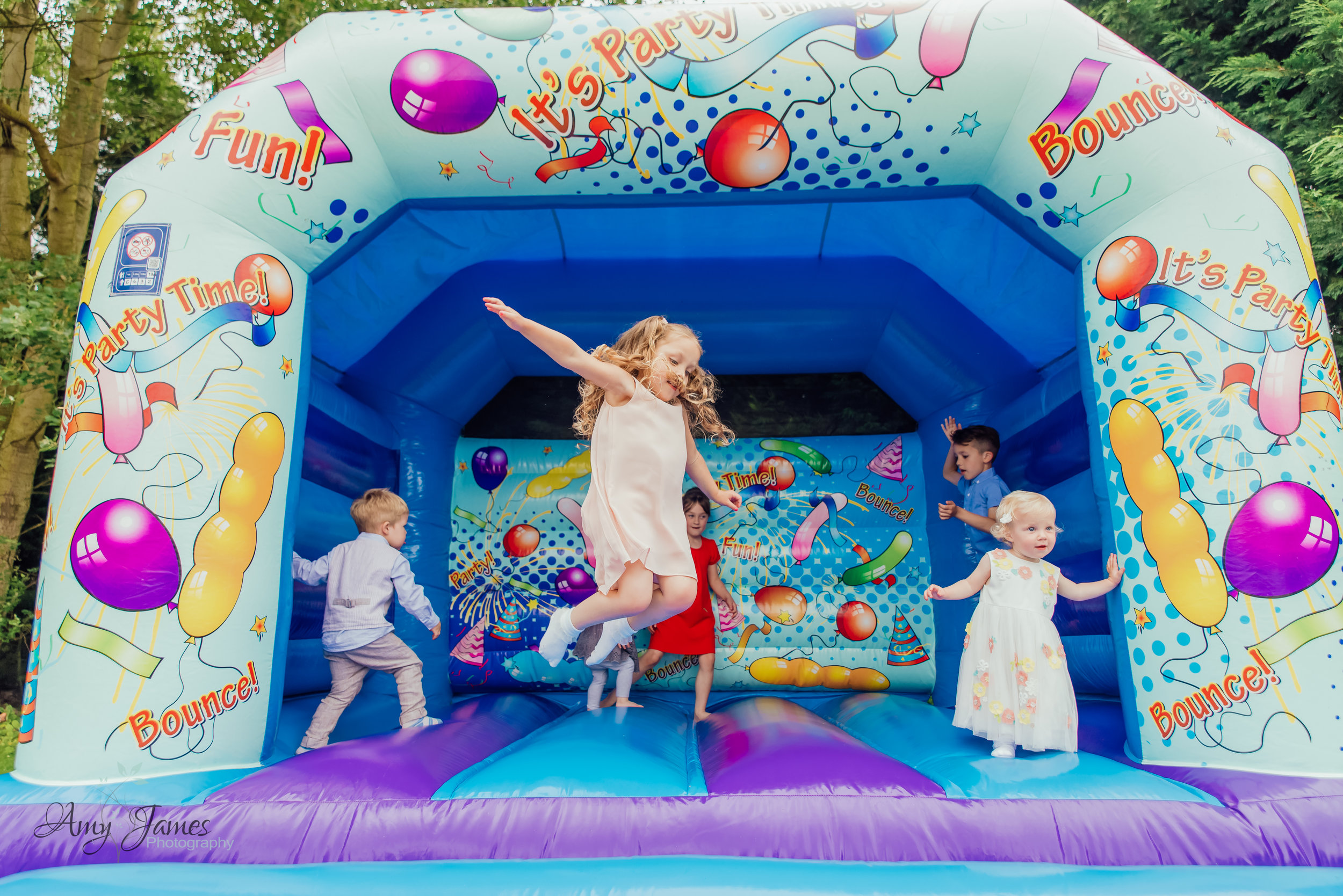 Child on bouncy castle at outside wedding venue Hampshire by Amy James Photography Hampshire and Surrey wedding photographer