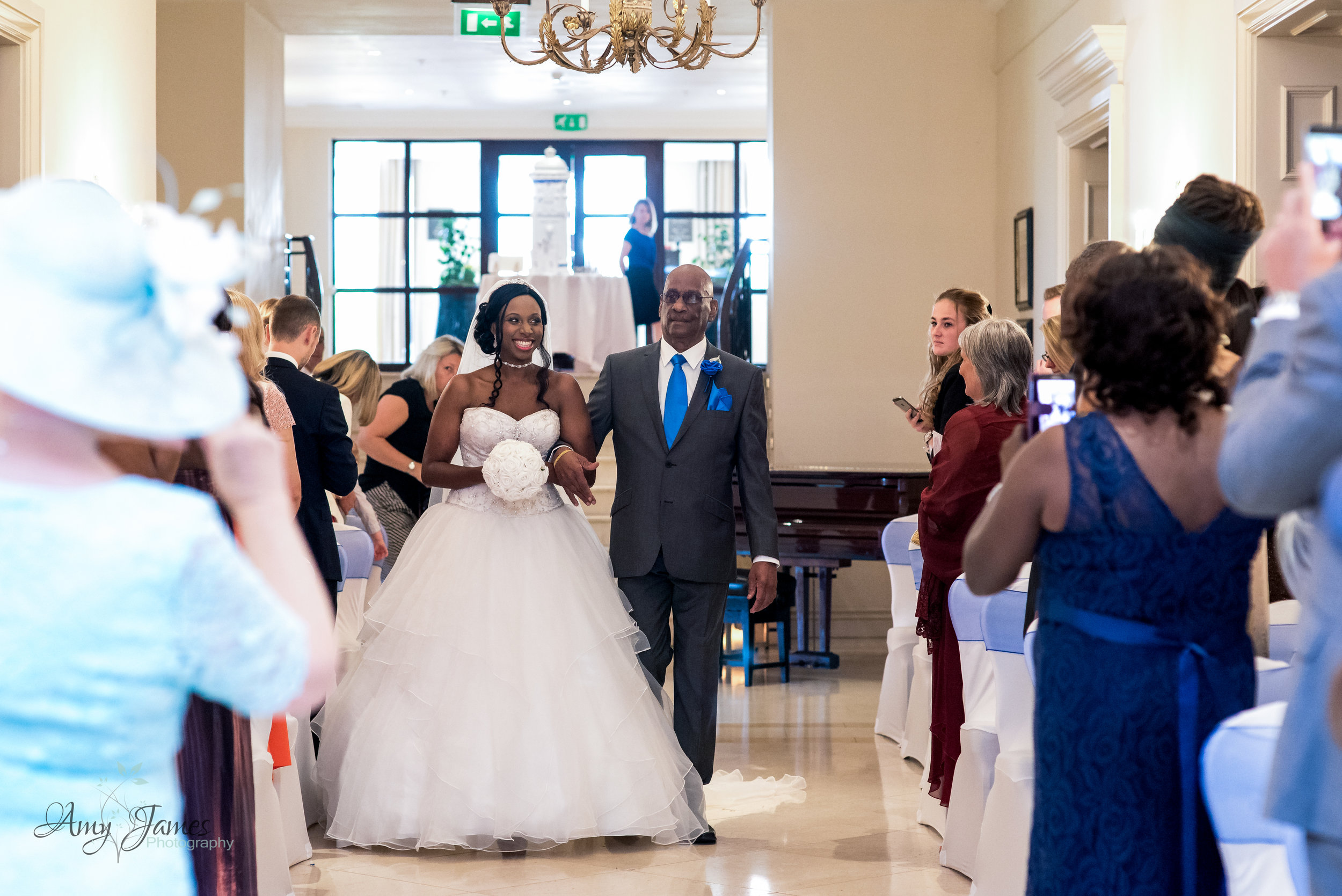 Bride walking down the aisle at Four Seasons Hotel Hampshire by Amy James photography - documentary wedding photographer for Hampshire and Surrey