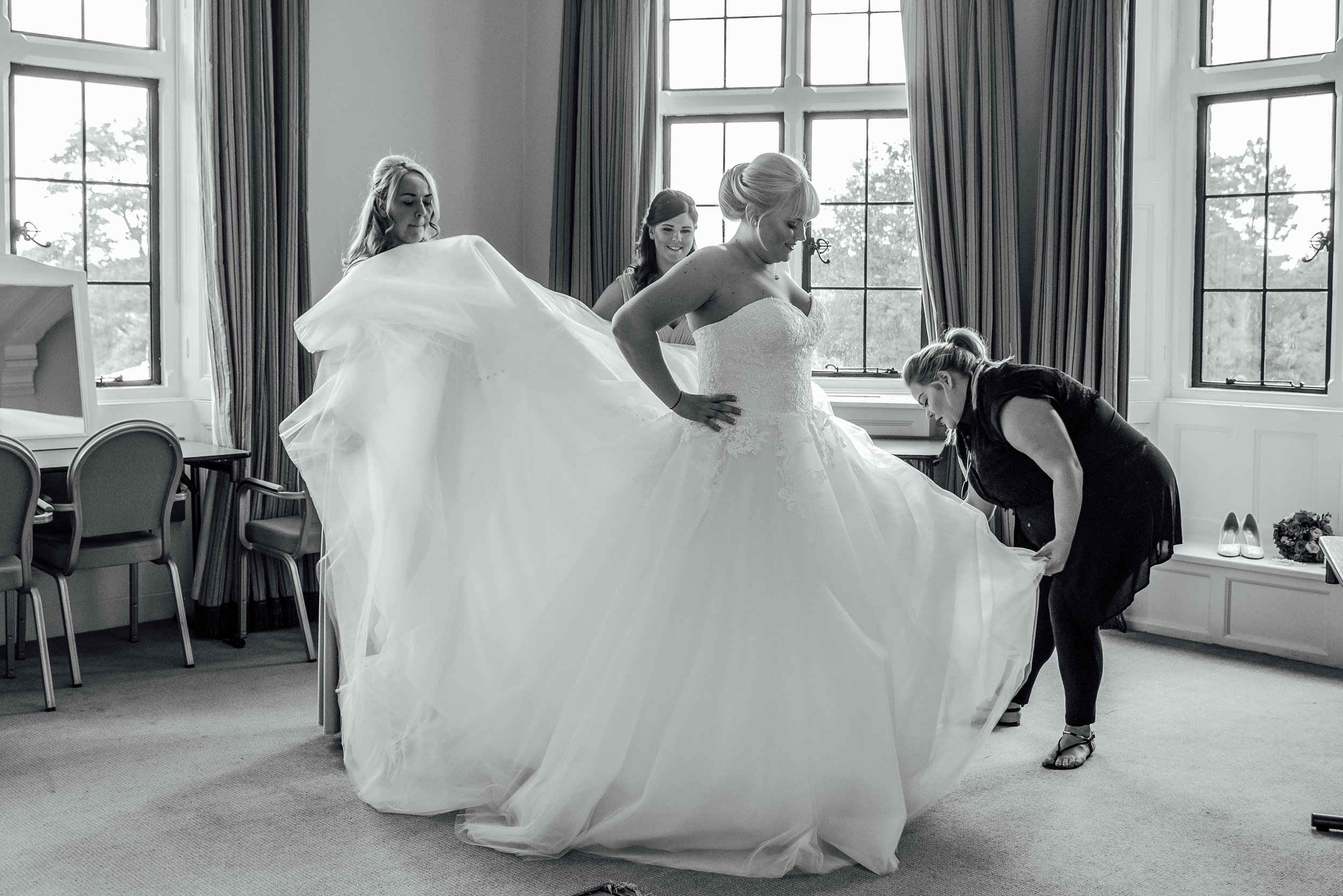 Bridesmaids helping bride into free at The Elvetham Wedding venue - by Amy James Photography- Hampshire Wedding Photographer