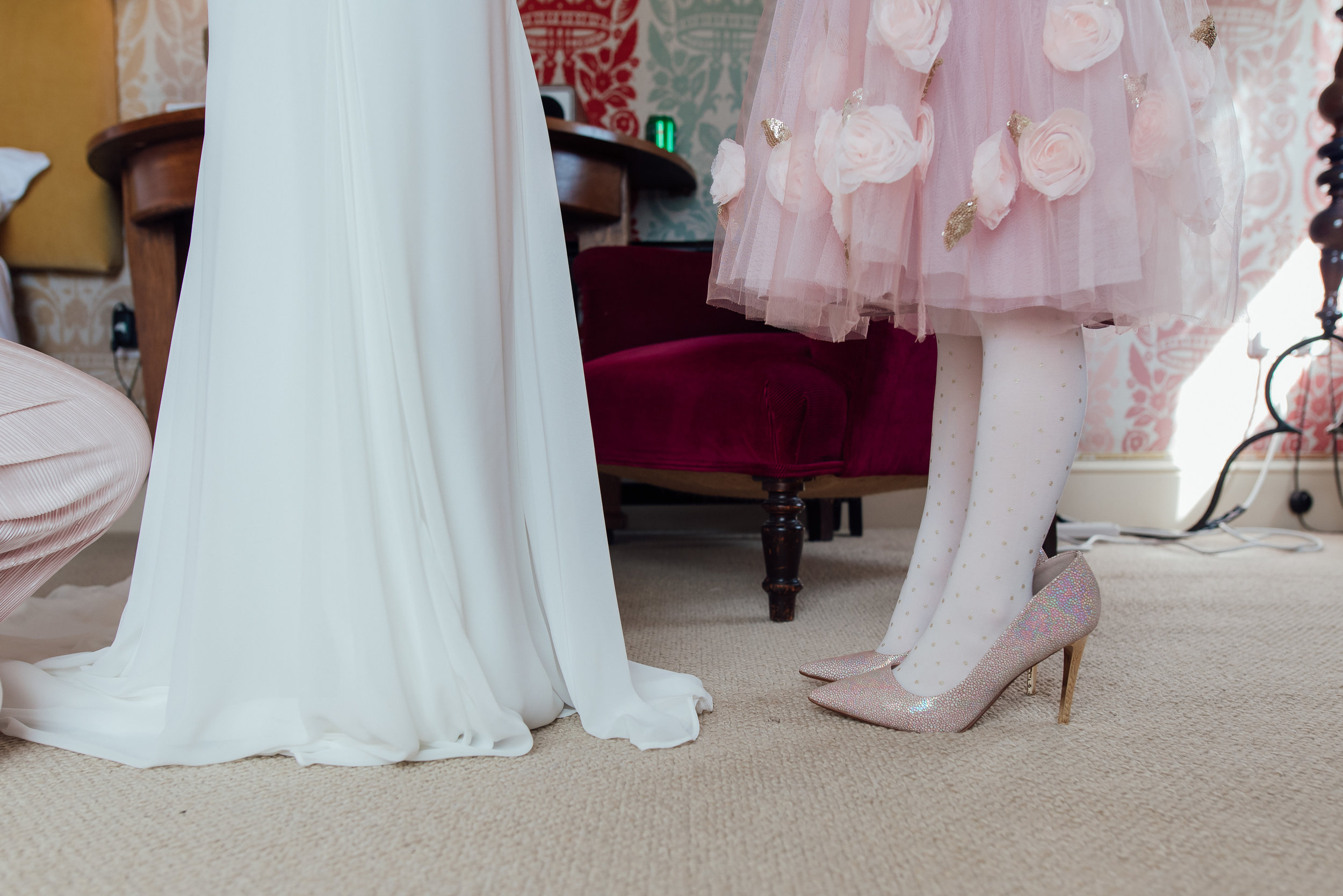 Flower girl wearing brides shoes at The George in Rye East Sussex Wedding Venue by Amy James Photography - Documentary wedding photographer Hampshire