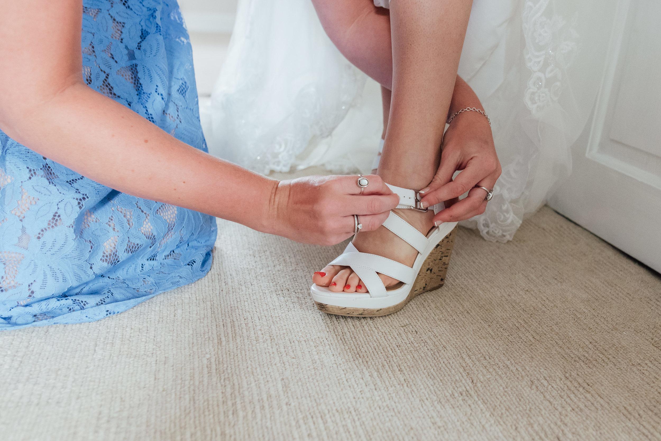 hampshire-wedding-photographer / Amy-james-photography / Hampshire-village-hall-wedding / village-hall-wedding / wedding-photographer-hampshire-surrey-berkshire / rotherwick-village-hall-wedding / Fleet -wedding-photographer / bridesmaid-doing-up-brides-shoe