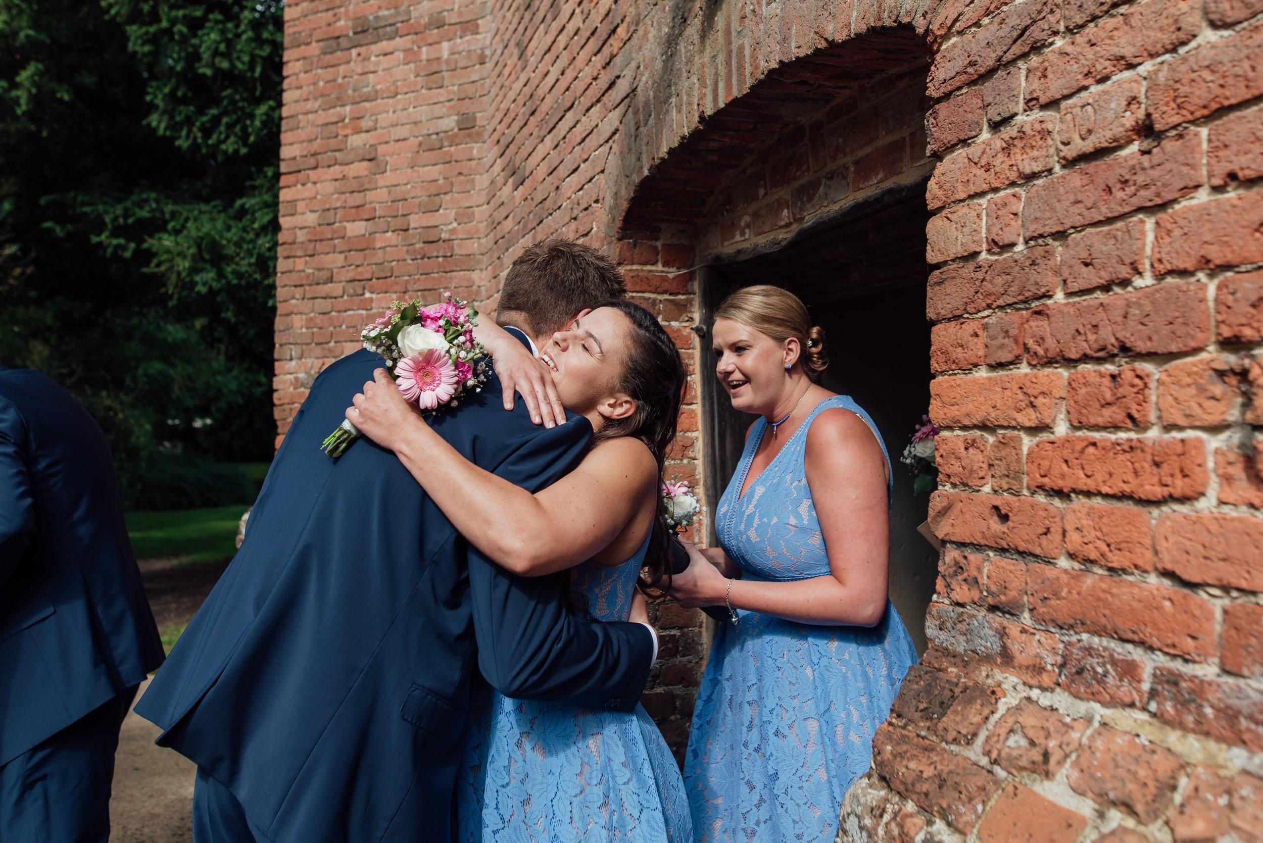bridesmaid-hugging-groom / rotherwick-village-hall-wedding / Amy-james-photography / wedding-photographer-hampshire