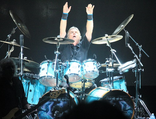 Kansas drummer Phil Ehart throwing his arms up at the end of the band's concert