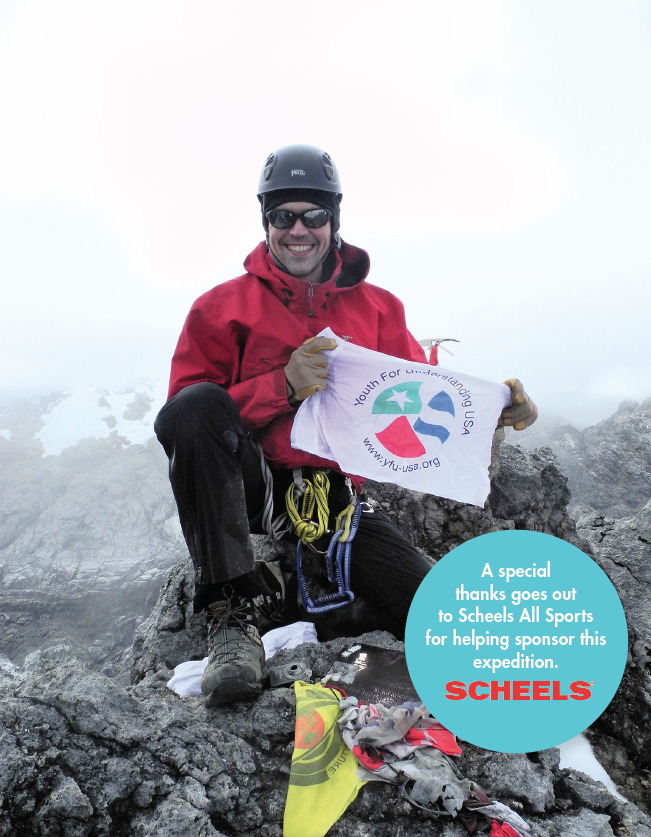 Andrew holds up a YFU flag atop Carstensz Pyramid, the tallest mountain on the continent of Oceania; July 2011.