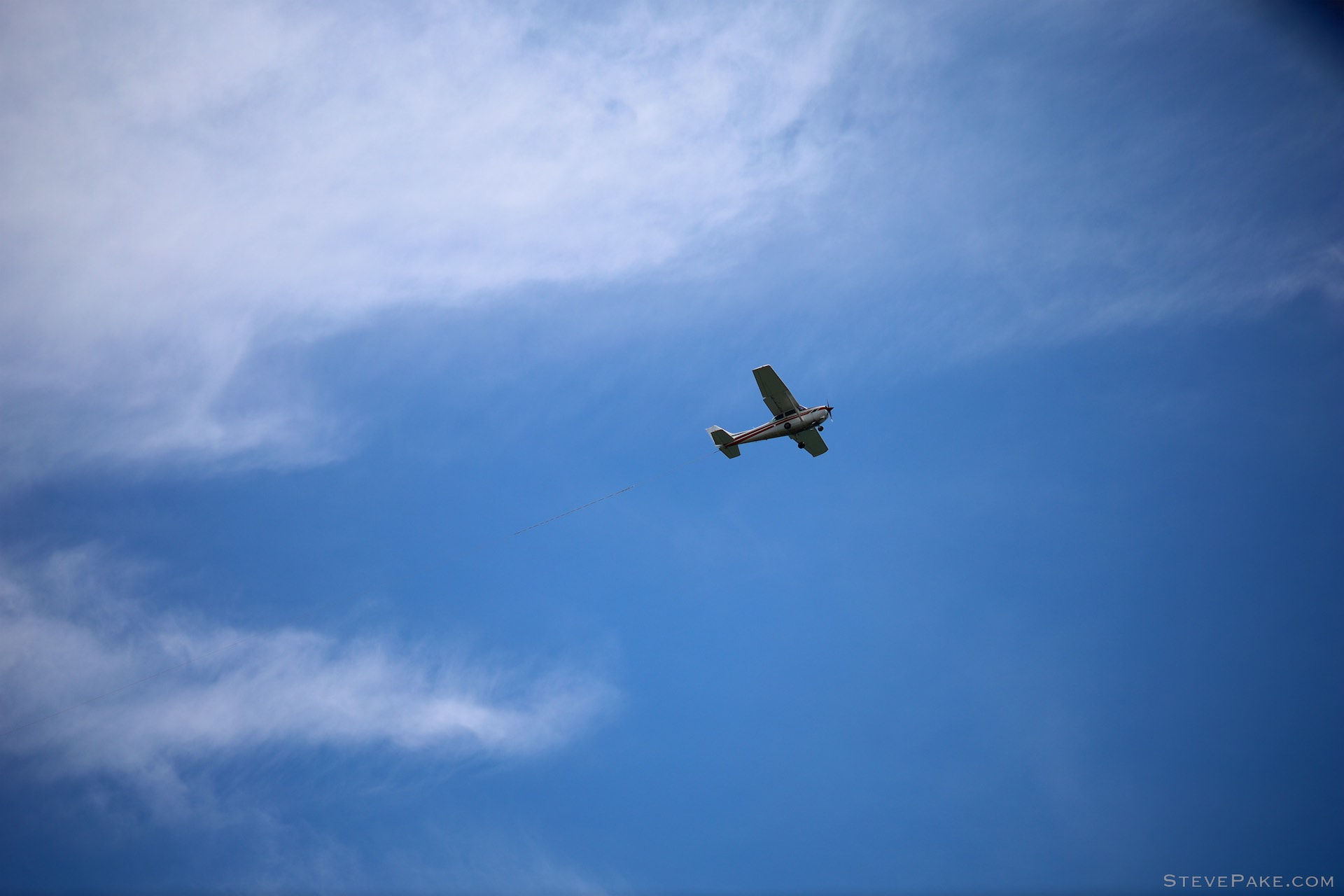 Banner tow plane at 135mm and f/2. What you're seeing here is the natural vignetting of the lens.