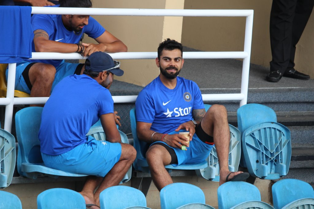 "India team captain Virat Kohli (bottom right) relaxes with teammates outside the players' dressing room during the fourth ""test"" match between India and the West Indies at the Queen's Park Oval in Trinidad in August 2016. They were waiting for the umpires to complete their inspection of the water-logged field. The game eventually was called off because of the adverse playing conditions. (Photo by Ewart Rouse. All rights reserved)"