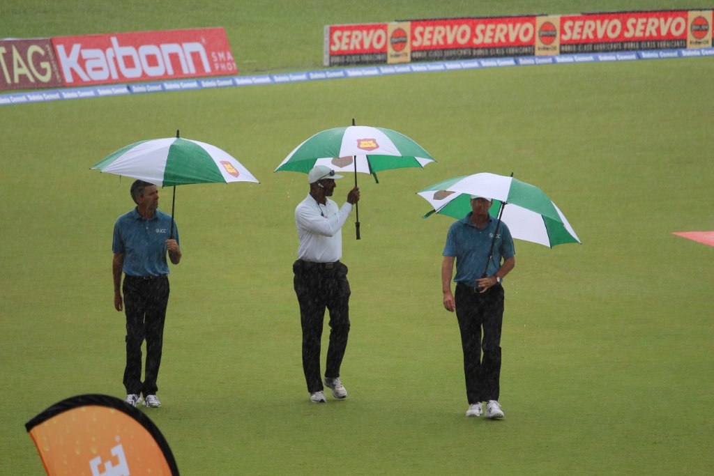 "Umpires for the fourth ""test"" match between India and the West Indies at the Queen's Park Oval in Trinidad in August are caught in the rain while inspecting the field following an earlier downpour. (Photo by Ewart Rouse. All rights reserved)"
