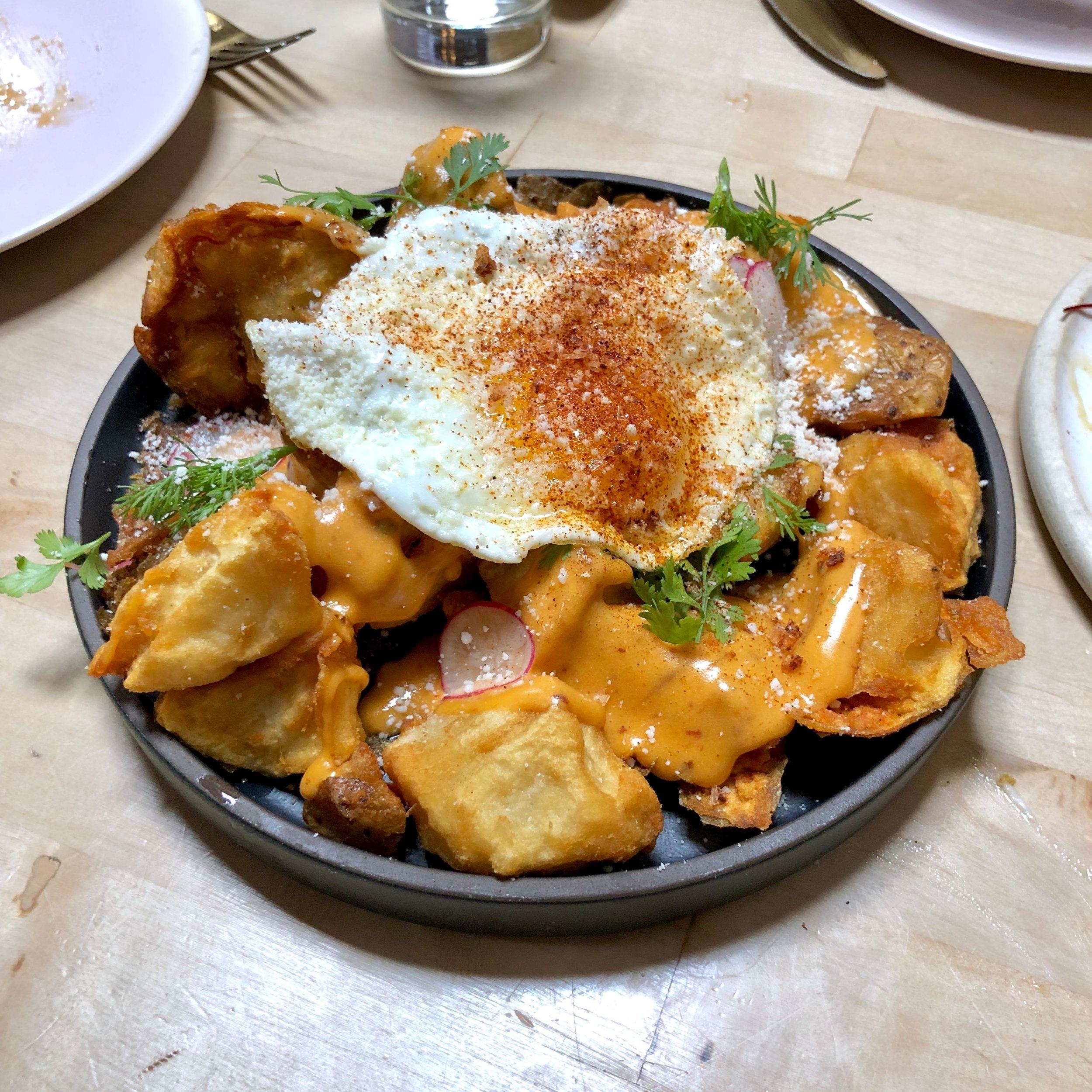 loaded crispy smashed potatoes // sunny egg, chipotle queso, salsa taquero
