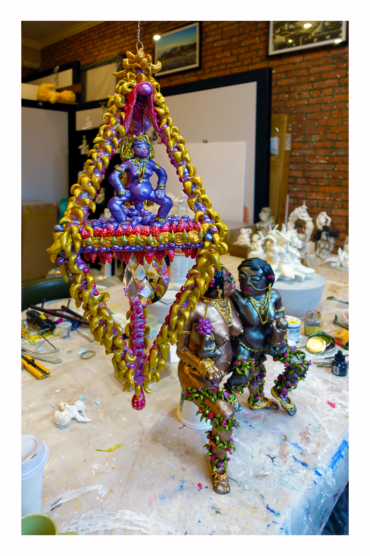 Abichandani's   suspended diamond sculpture symbolizing the   female triangle of life   with a goddess giving birth.  On the table is a sculpture of a same sex female couple representing some of the artist's friends who recently gained the right to lawfully raise families as a union.