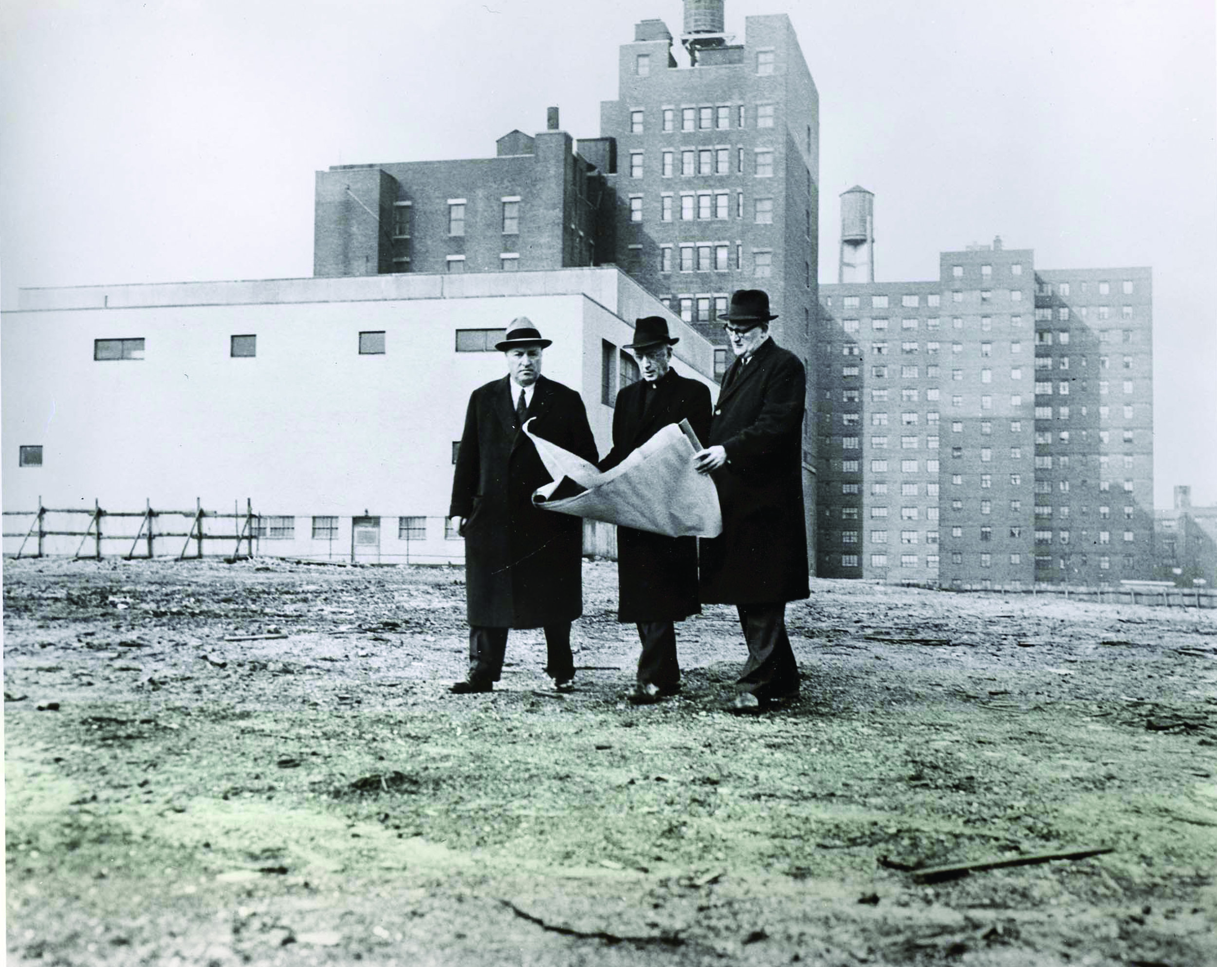 Fordham trustee Joseph A. Martino; Laurence J. McGinley, S.J., president of Fordham; and Fordham Law Dean William Hughes Mulligan at the site of the Lincoln Center campus, 1959.