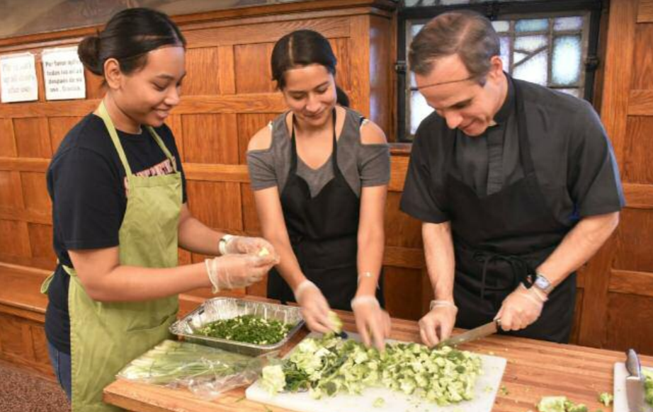 Fr. Rocco Danzi, S.J., vice president for Mission and Ministry, helps prepare food with student volunteers at the Saint Peter's University Campus Kitchen.