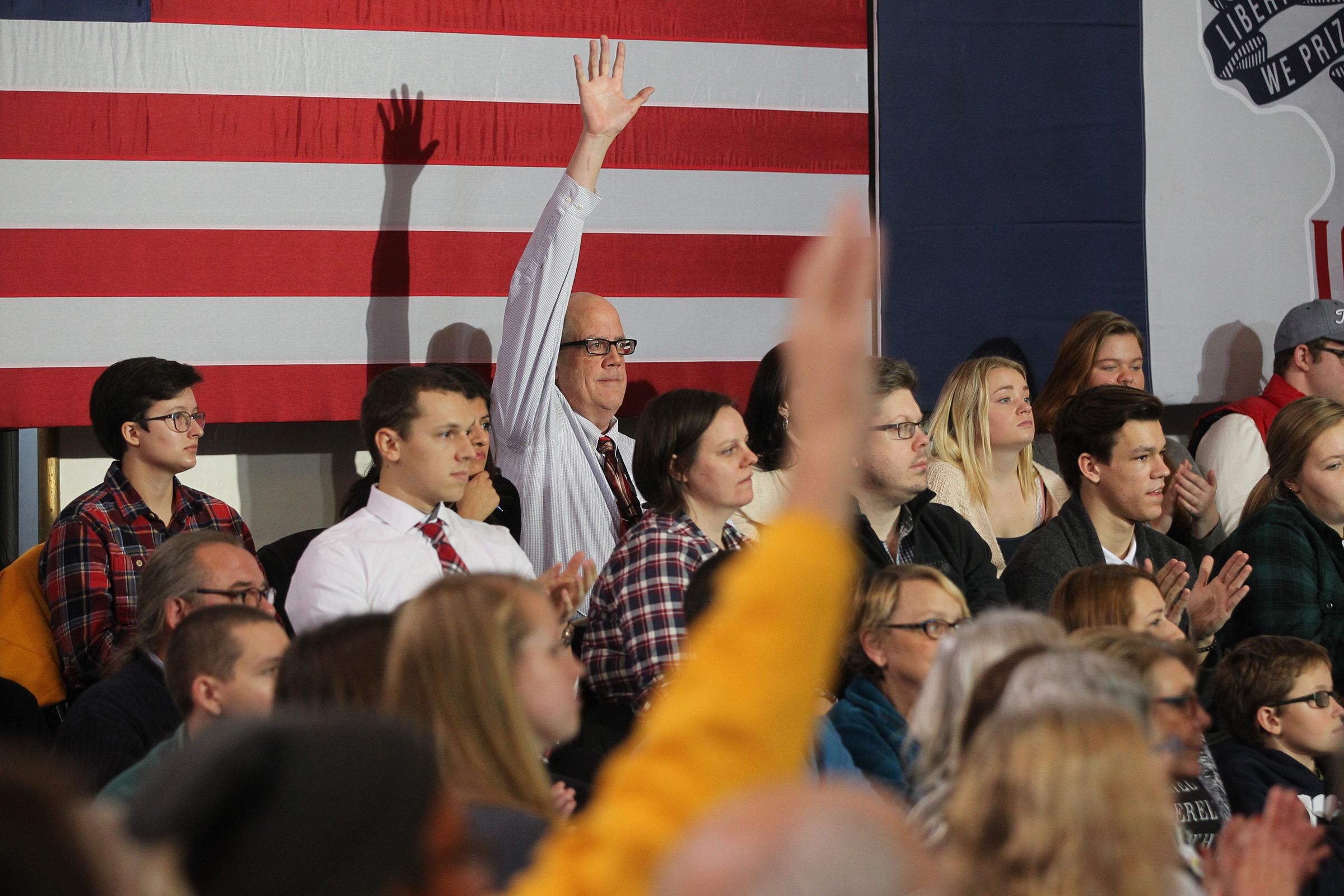 A man raises his hand as Democratic presidential candidate Hillary Clinton looks for questions at Old Brick Church.