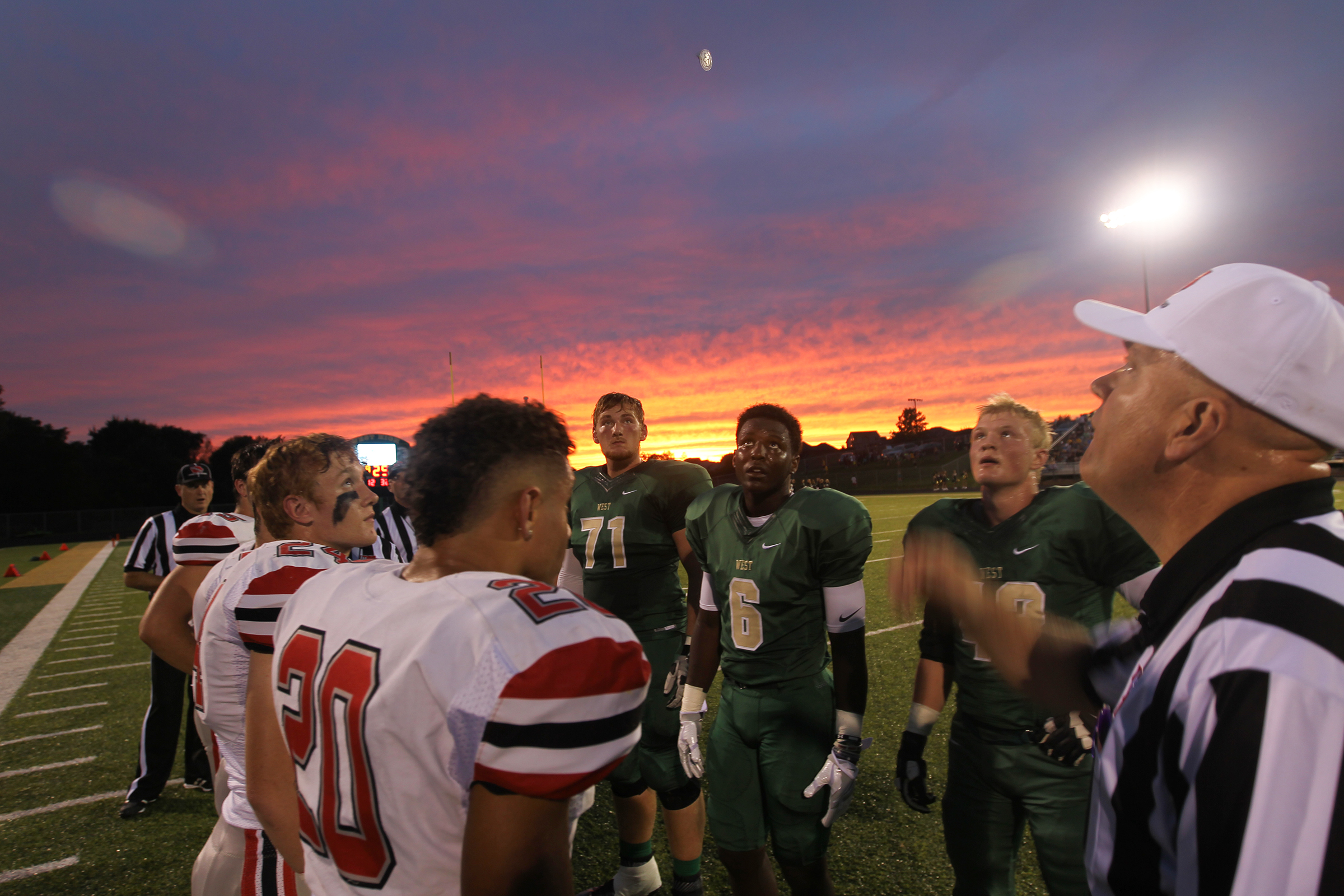 City High and West High players line up for the coin toss before their game at West High.