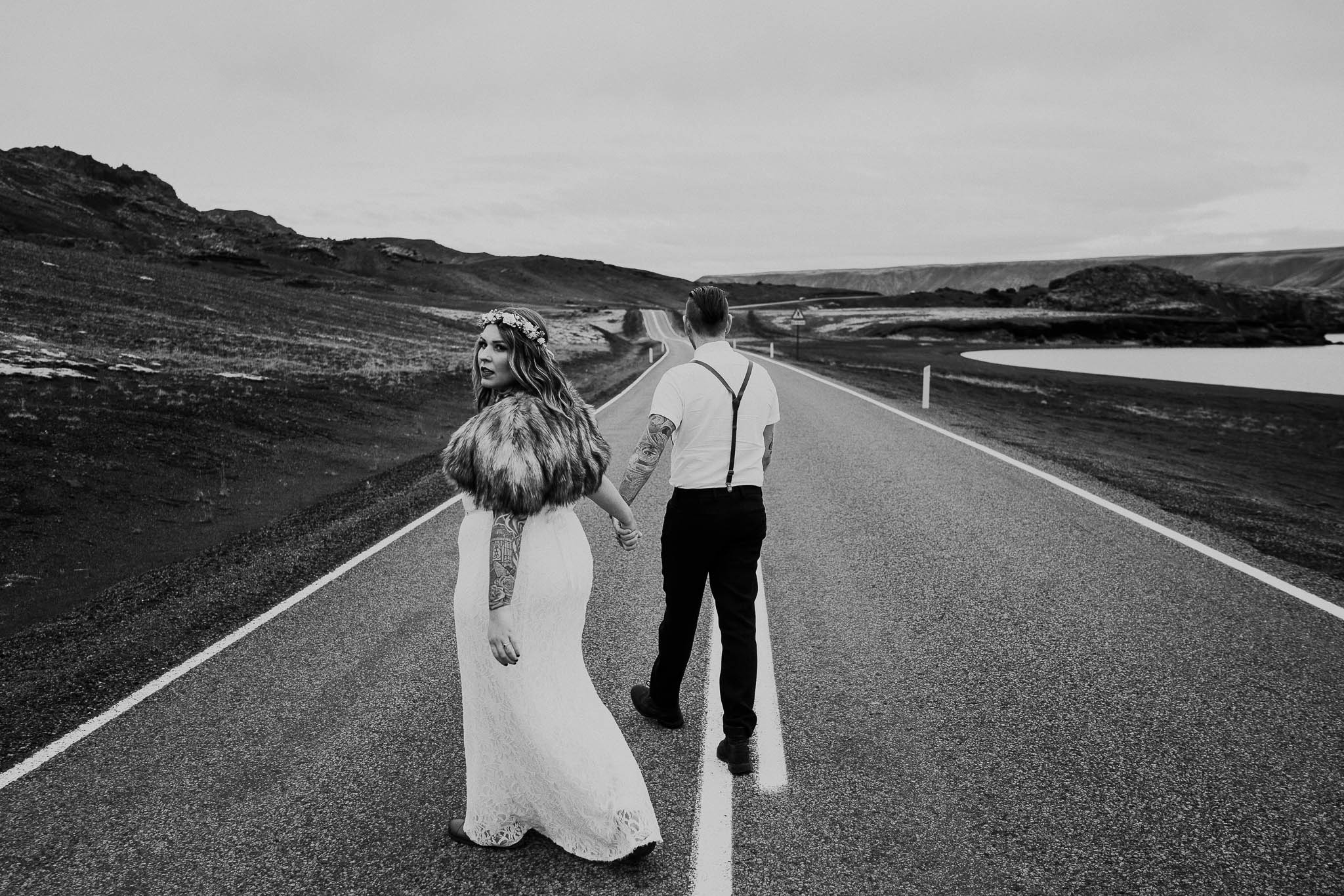 couple walking along a road in iceland