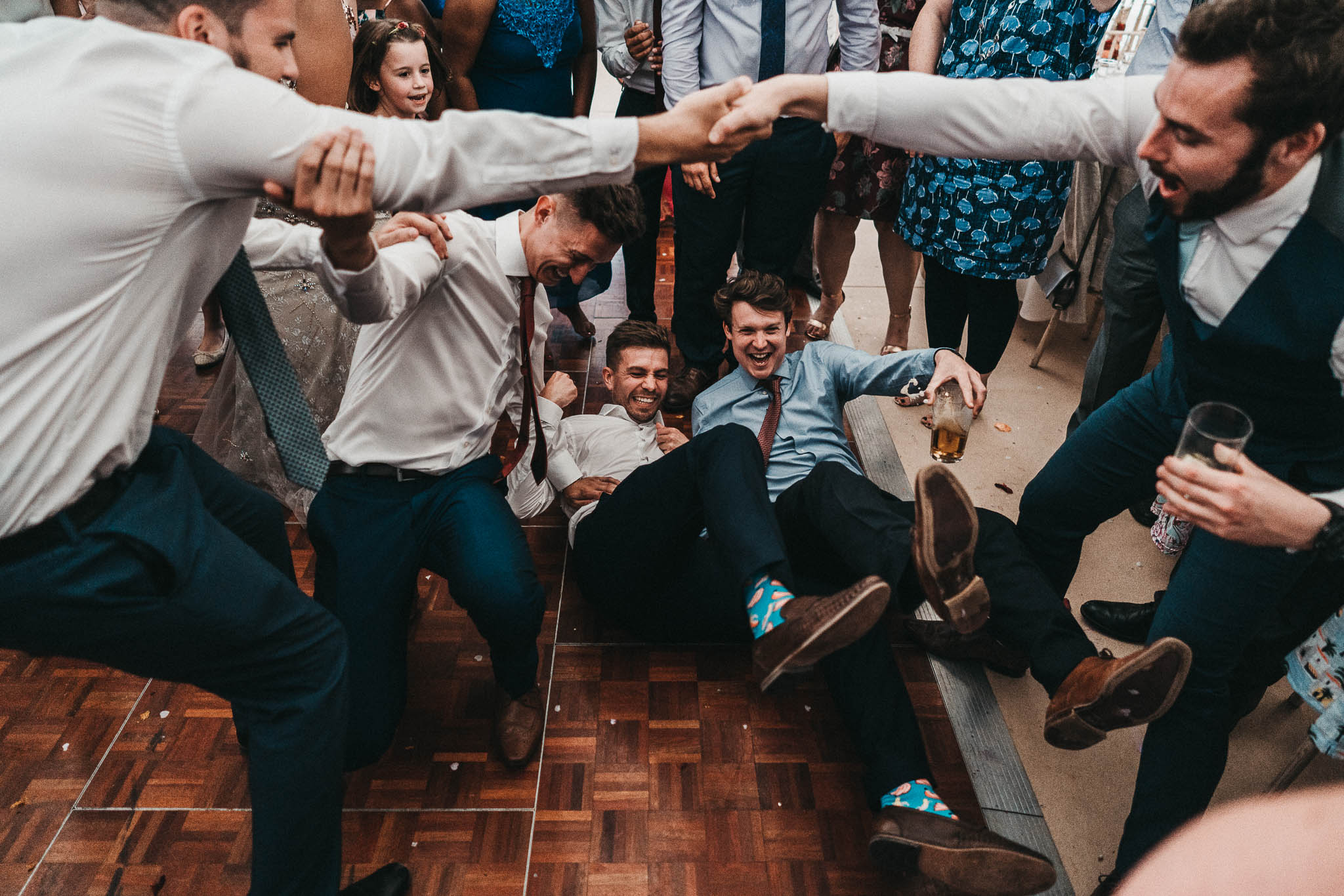 funny picture of people falling over on dancefloor at a wedding
