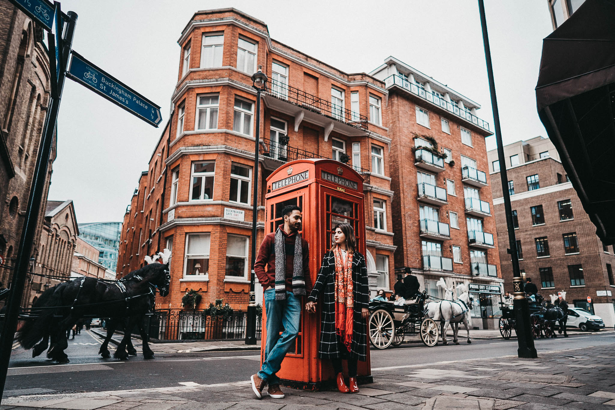 couple standing near a phone box for a photoshoot