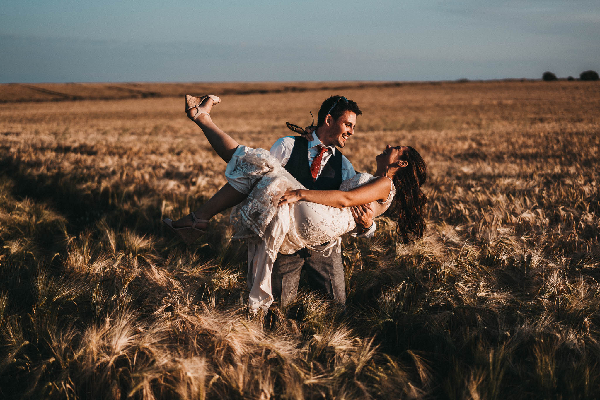 bride being lifted up in a wheat field