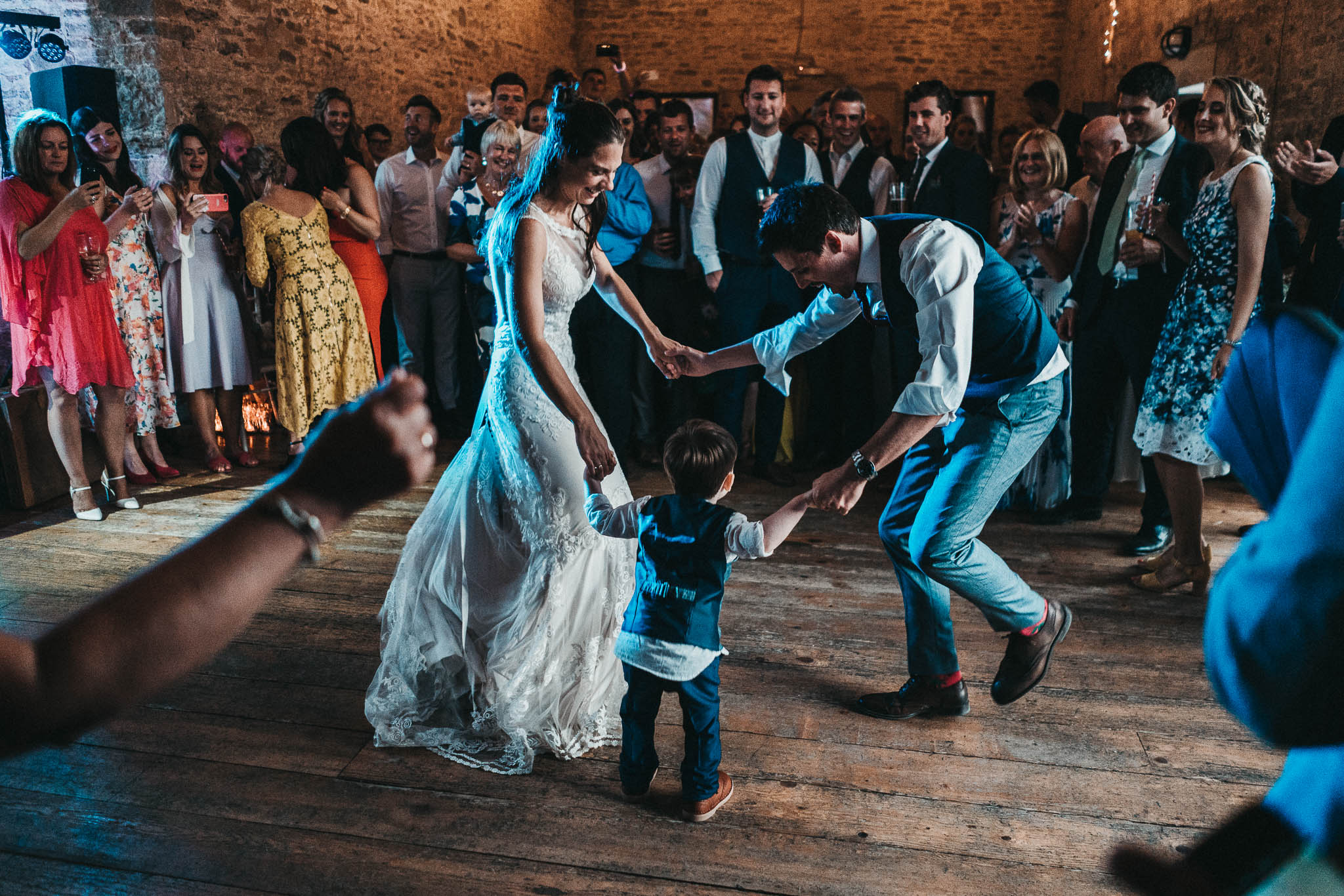 bride and groom dancing with little boy