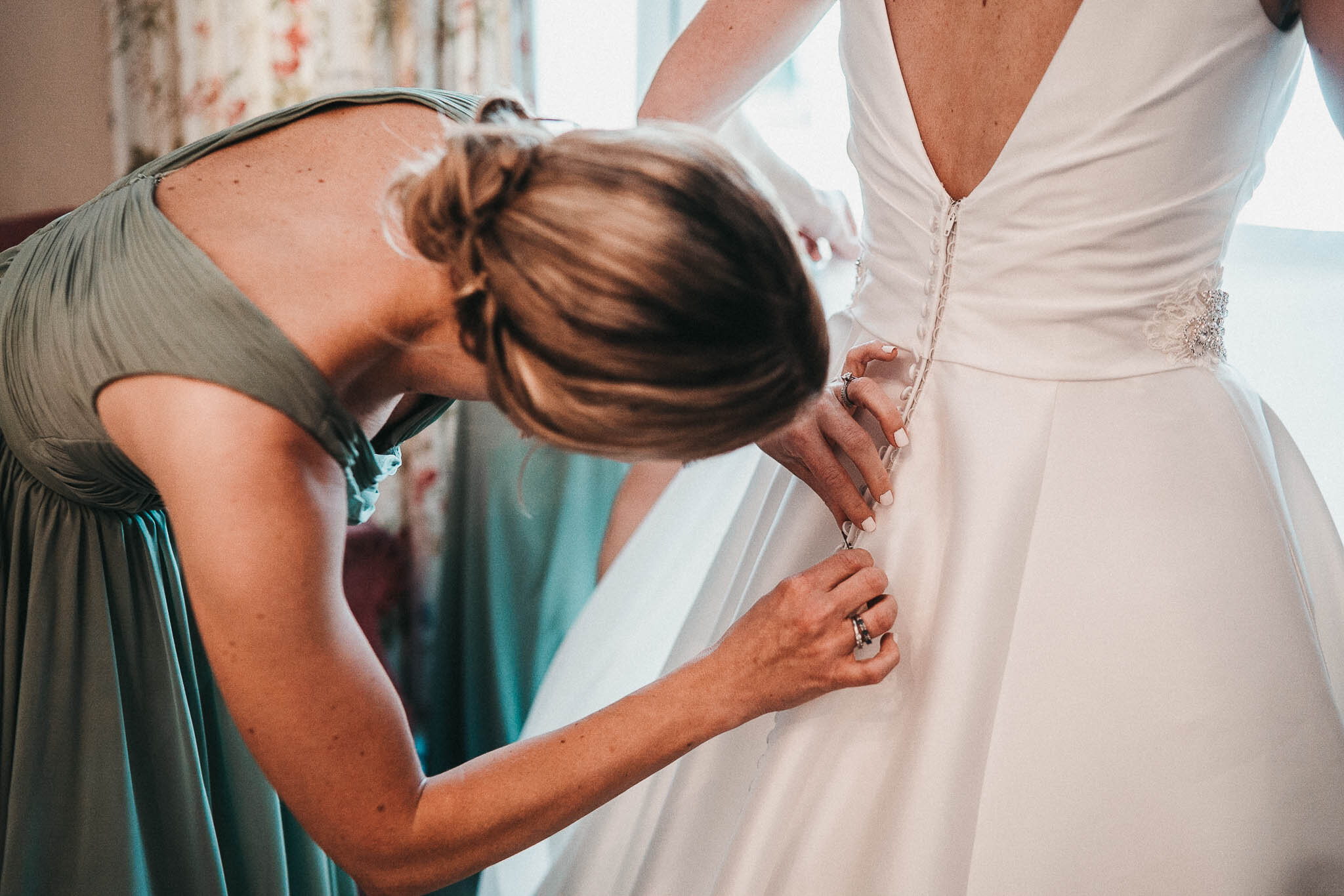 bride-having-dress-adjusted-by-bridesmaid