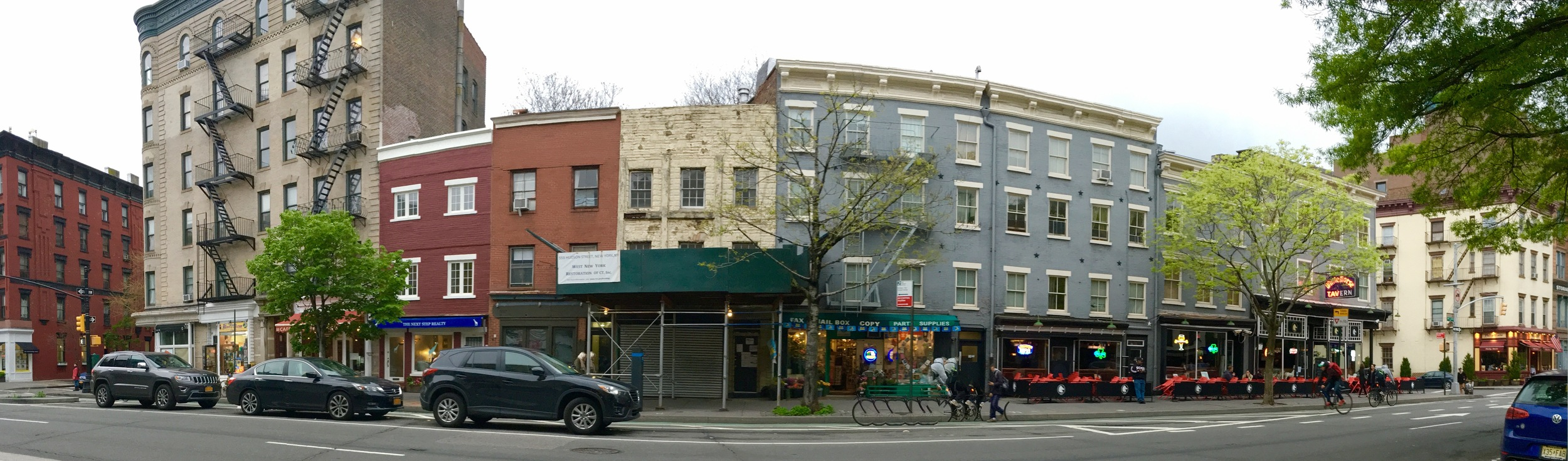 "Jane Jacobs's ever-changing West Village block, the site of the famous ""sidewalk ballet,"" on May 3, 2016. Jacobs's home, 555 Hudson Street, is the dark red one. At the end of the block on the right is the White Horse Tavern. Photo by the author."