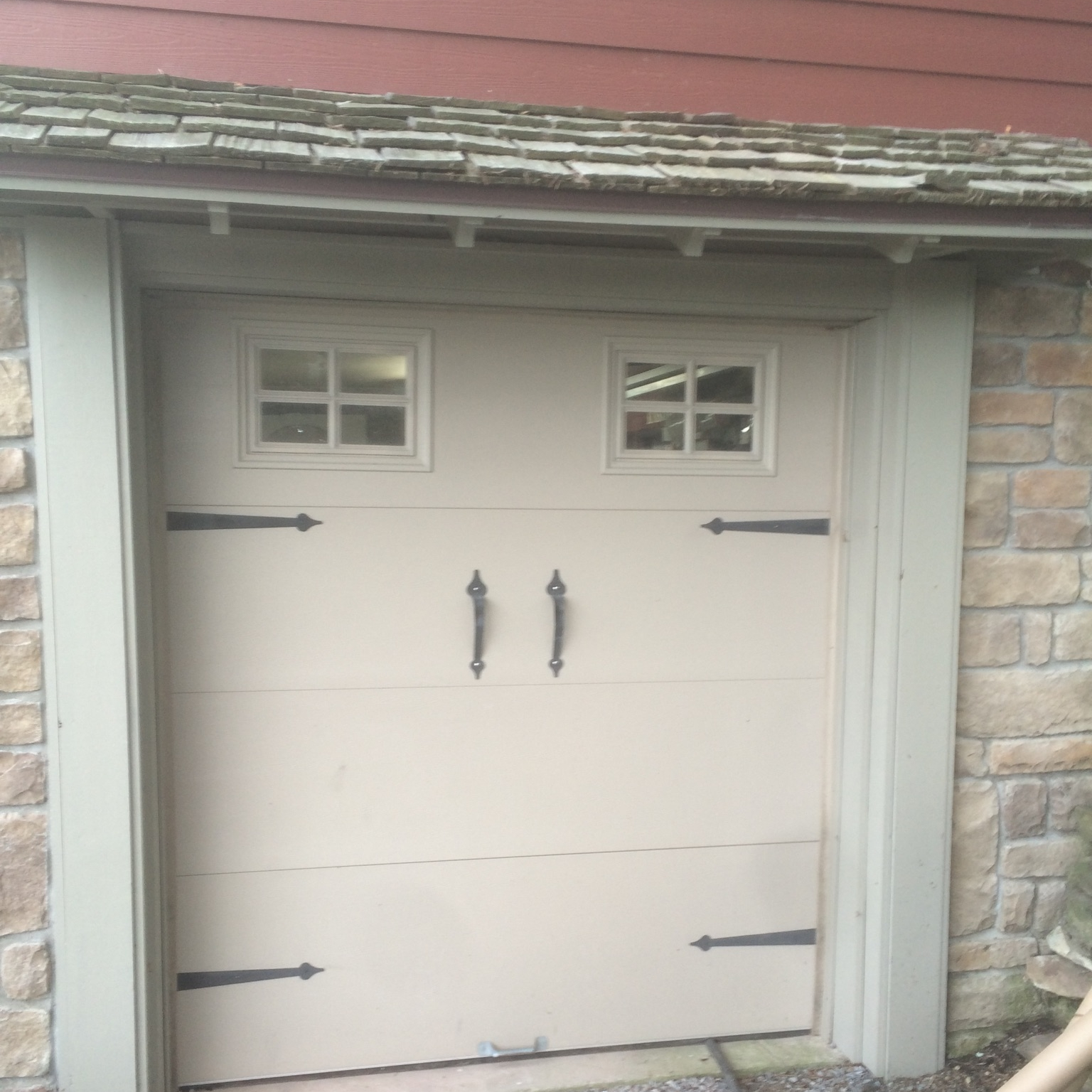 "This was our ""garage"" door before we started. To say it was a garage wasn't really true. I doubt we could have fit anything larger than a Smart Car through this tiny thing."