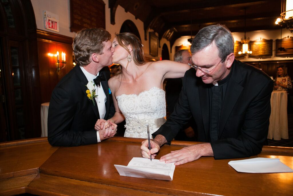 signing our marriage license at the bar while kissing my husband with my arm around a priest... lots happening here.