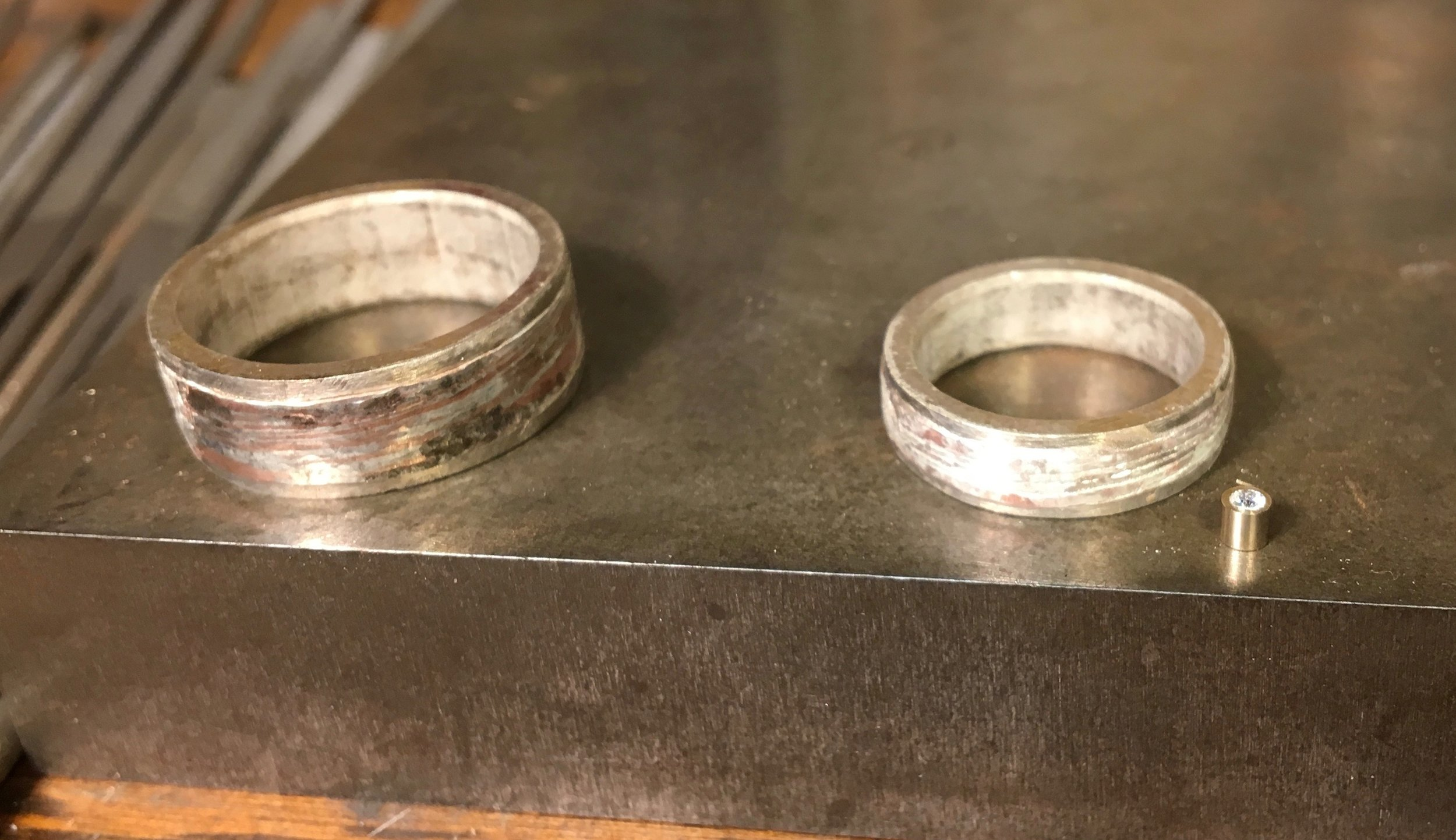 Then soldered in place.... Here the rings are shown with a 14k white gold bezel and diamond that is due to be put into Jayne's ring.
