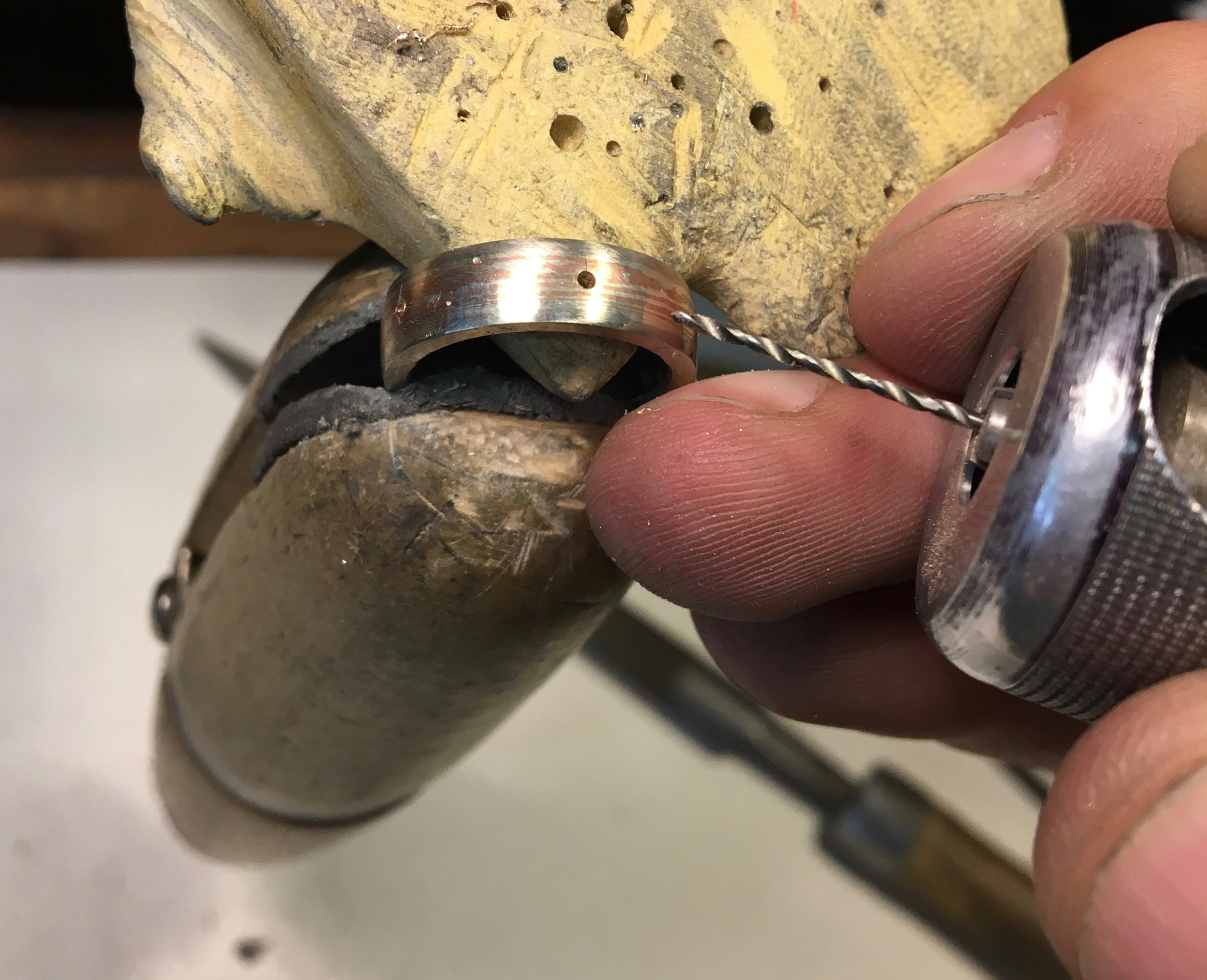 In this picture Jayne's ring has been filed and sanded and the placement of the stones has been marked. I'm now drilling the guide holes for the settings.