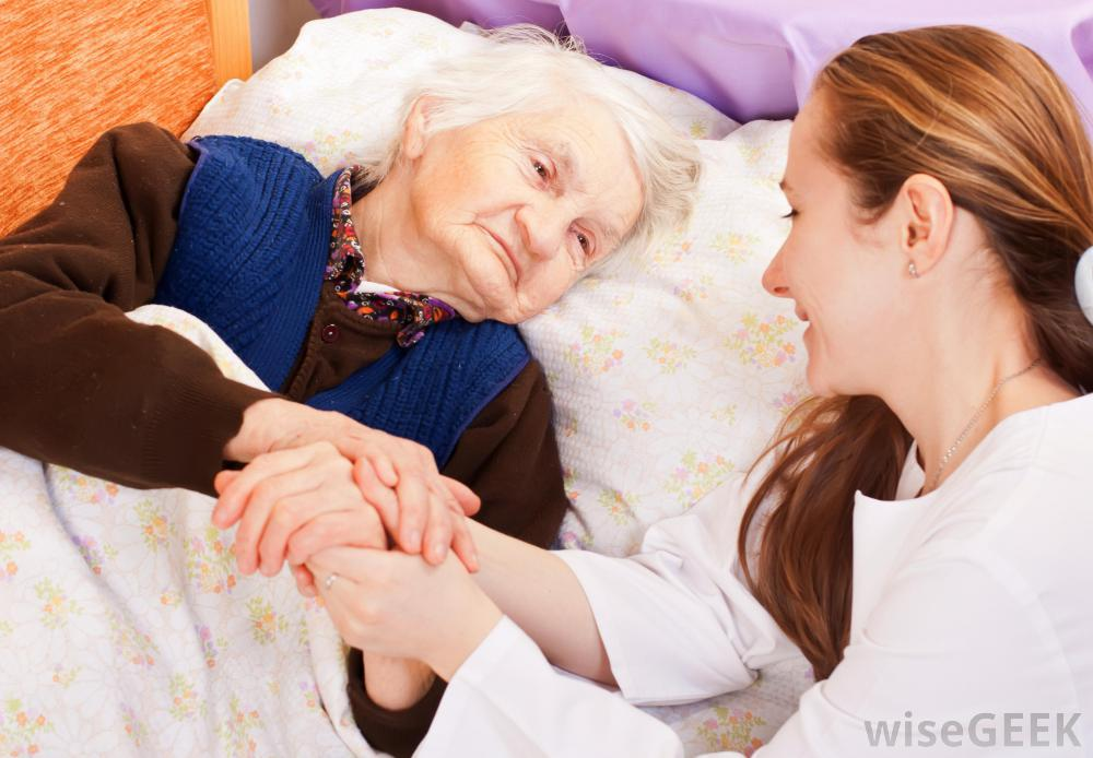 old-woman-lying-in-bed-holding-hands-with-young-woman.jpg
