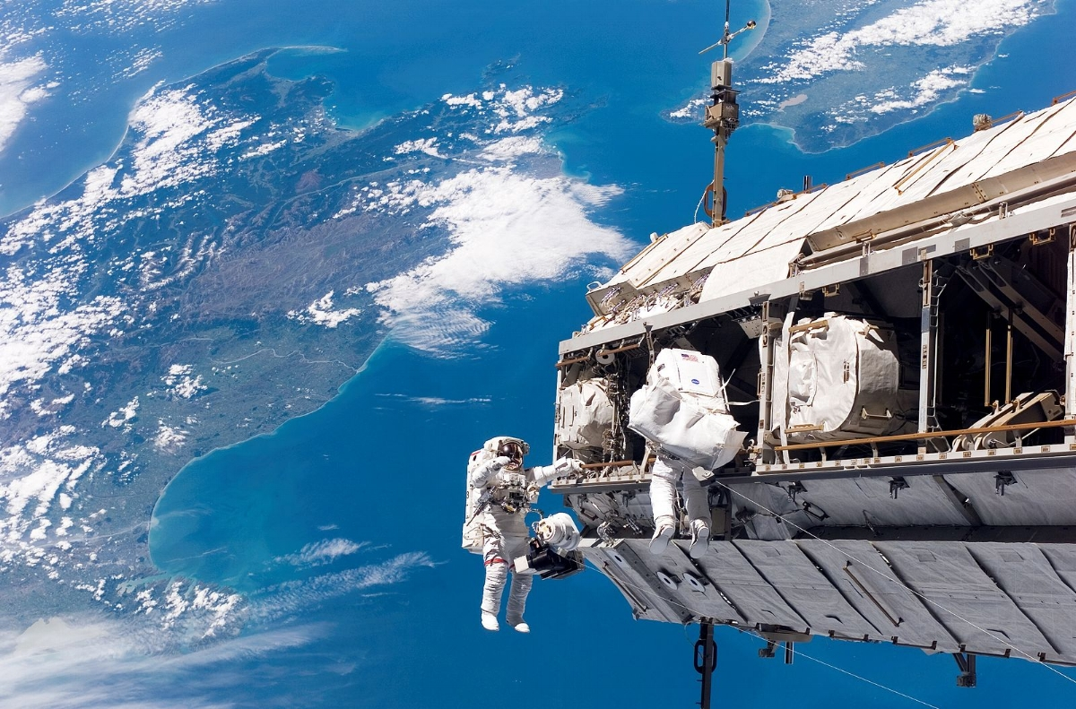 """Backdropped by a colorful Earth, astronaut Robert L. Curbeam, Jr. (left) and European Space Agency (ESA) astronaut Christer Fuglesang, both STS-116 mission specialists, participate in the mission's first of three planned sessions of extravehicular activity (EVA) as construction resumes on the International Space Station. The landmasses depicted are the South Island (left) and North Island (right) of New Zealand."""