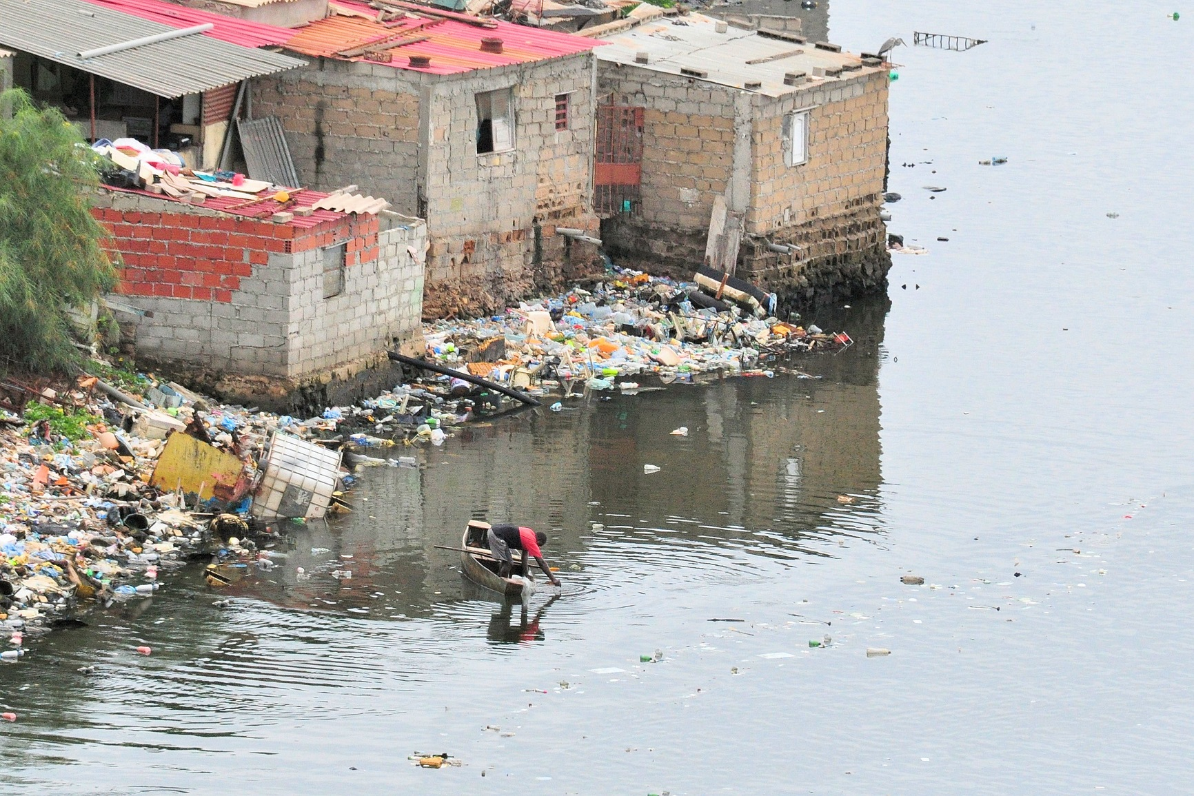 Not far from the bustling streets and high rise buildings of Angola's capital city of  Luanda , this man catches fish in a polluted lagoon surrounded by shanty towns.