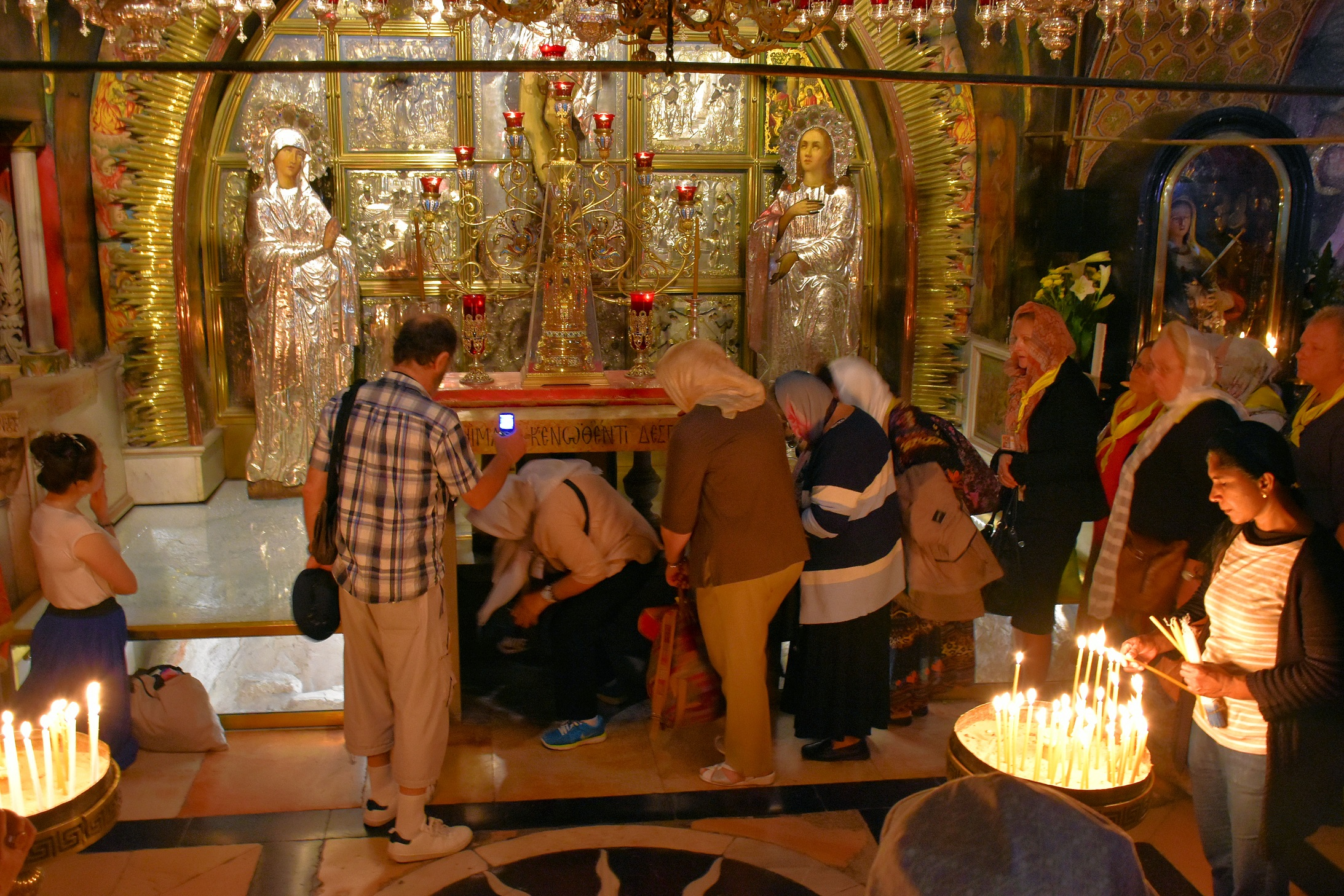 At the Altar of the Crucifixion, devoted Christian pilgrims in the Church of the Holy Sepulchre bend down to touch the rock where, according to tradition,the cross of Jesus once stood.