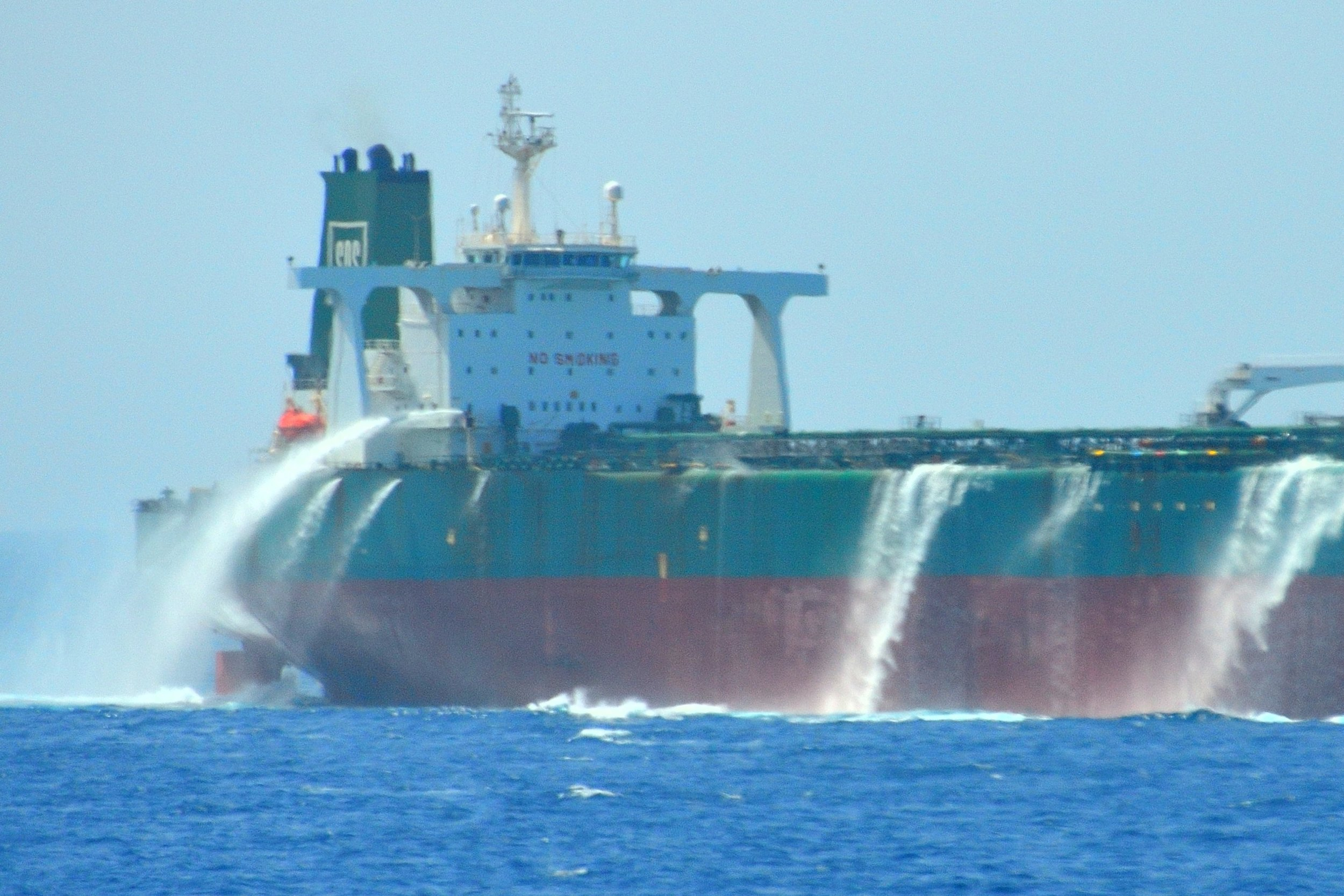 The crew of an oil tanker perform a piracy drill in the Gulf of Aden off the coast of Somalia. Pirates are deterred from boarding by large volumes of water being poured over the sides of the ship.
