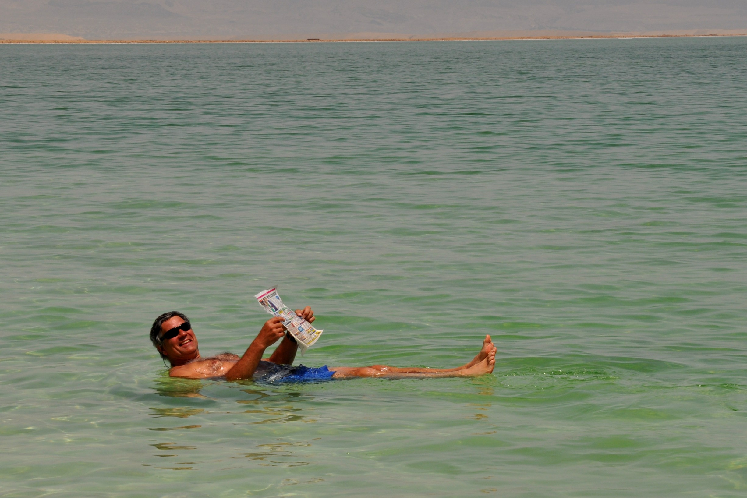 "The thing to do when ""swimming"" in the Dead Sea: reading newspaper while floating in buoyant waters."