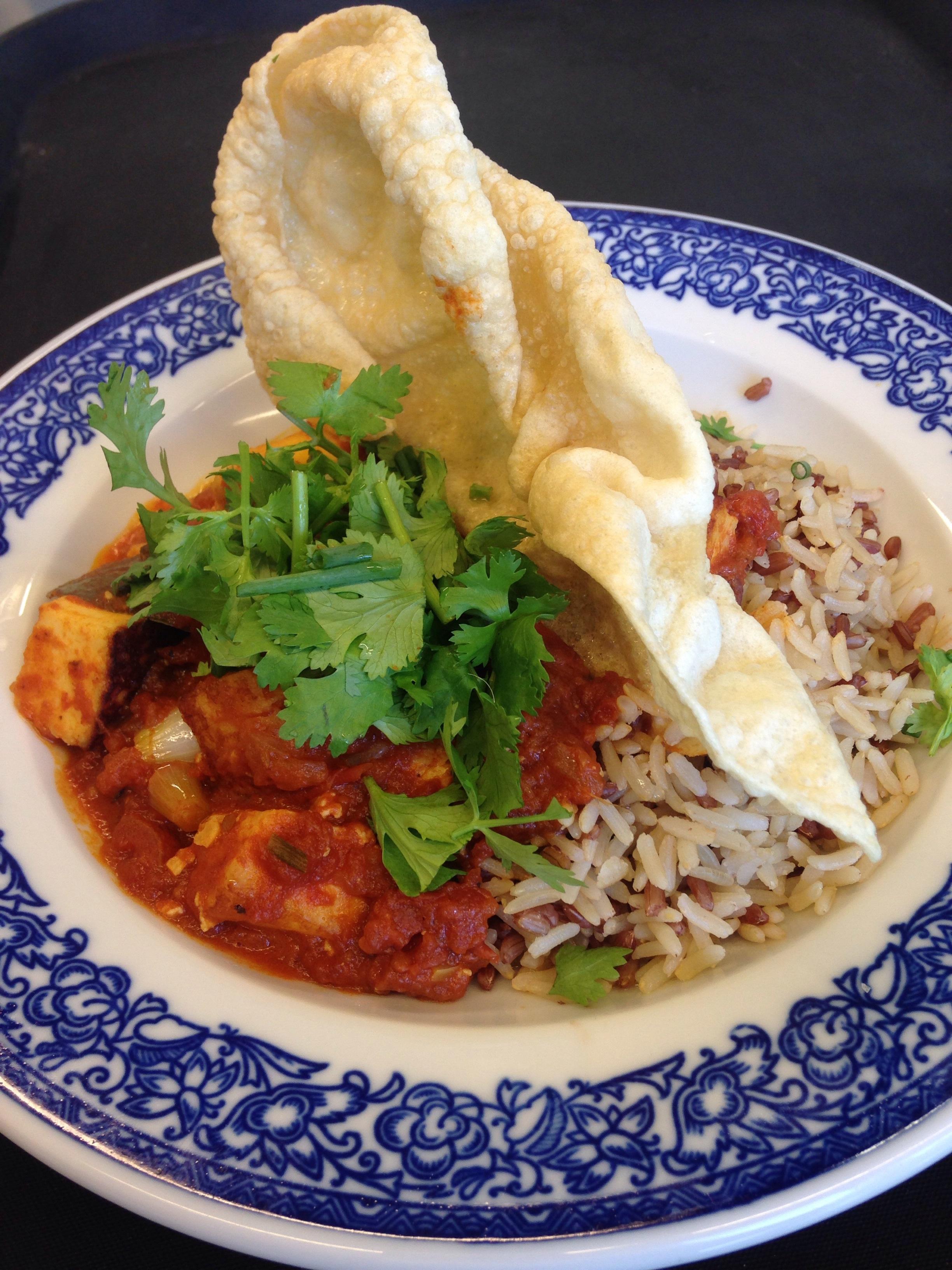 Paneer an cremiger Tomatensauce (indisch gewürzt) mit Vollreis, Koriander und Pappadam