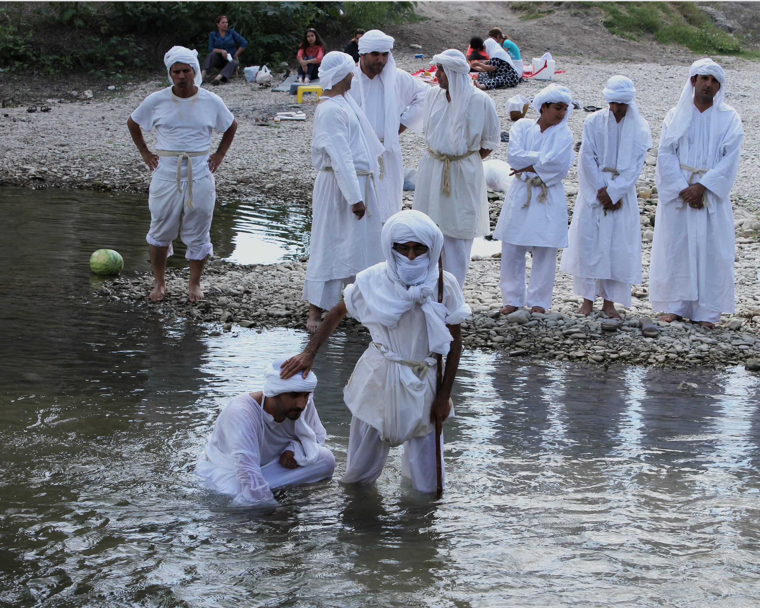 Community members watch a baptism in progress. The Mandaeans believe in non-violence and they avoid altering their body, which means some members don't cut their hair. Their minority status has led to centuries of persecution. There were around 60,000 Mandaeans living in Iraq in 2003. Now there are less than 5,000.