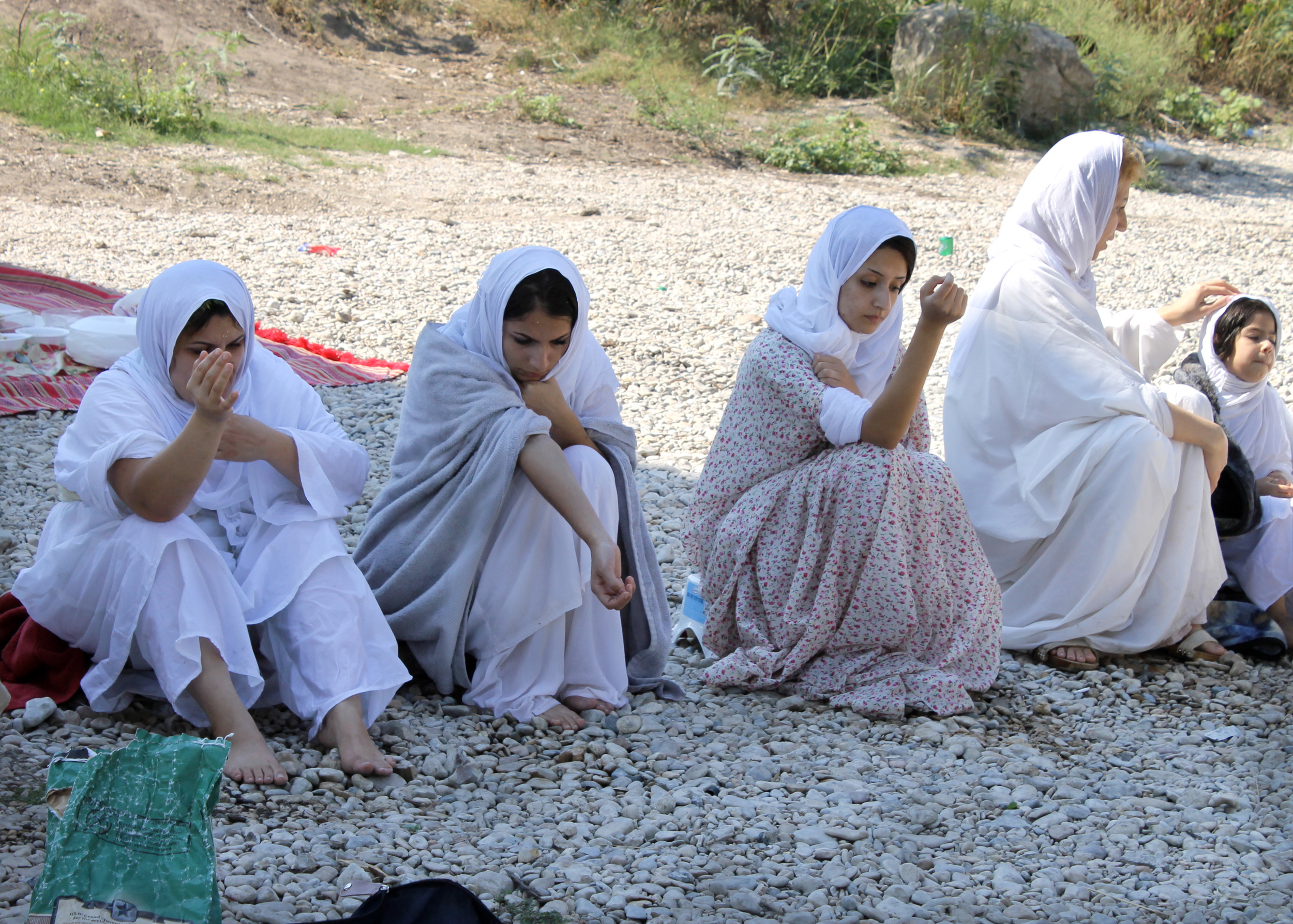 Community members wrap themselves in blankets to keep warm after the baptism is finished. Here, three generations of the same family sit together.