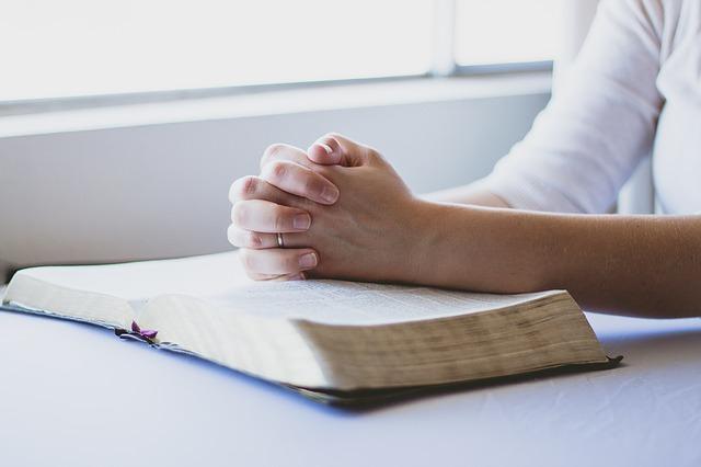 woman praying with open Bible