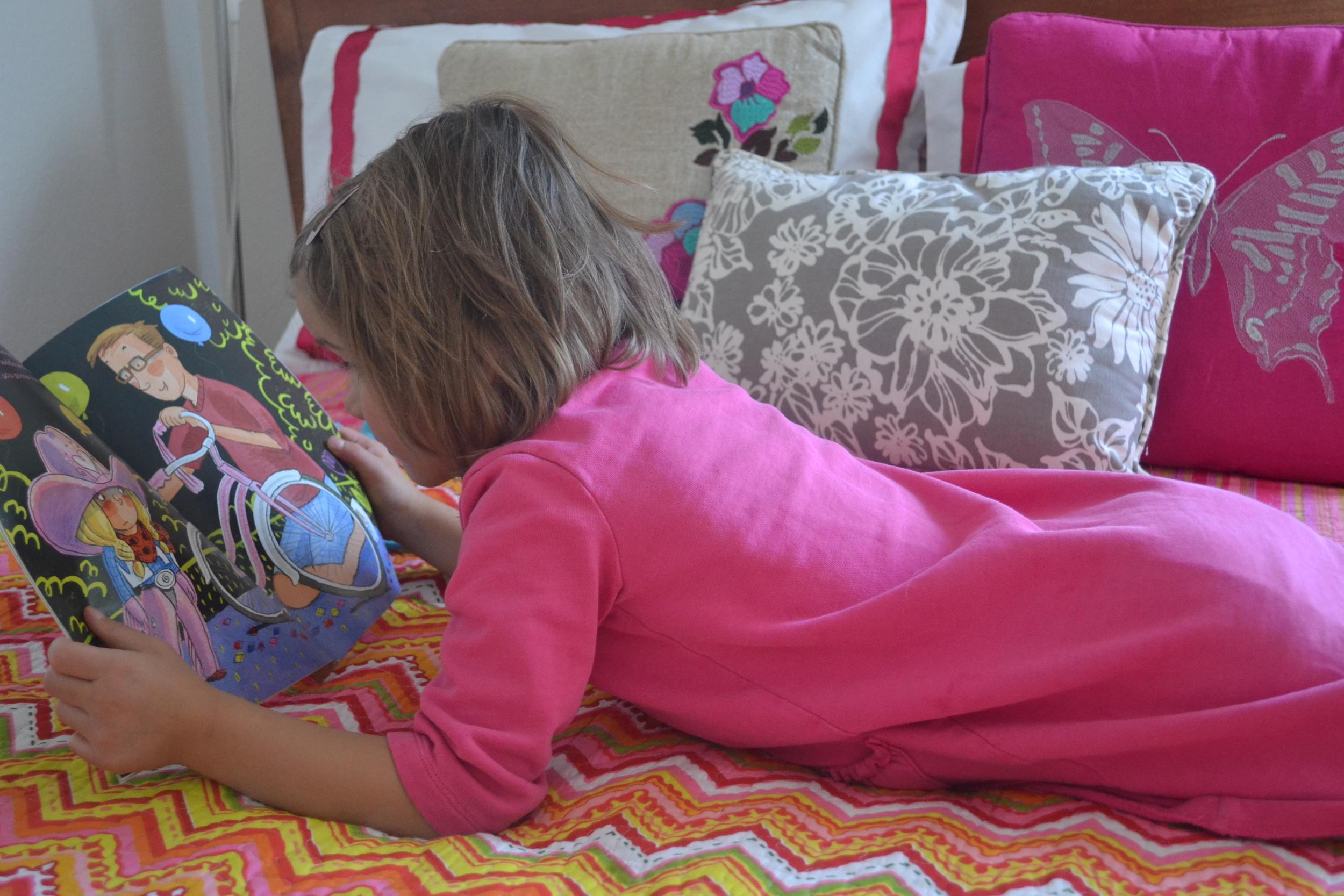 A little girl reads a children's book