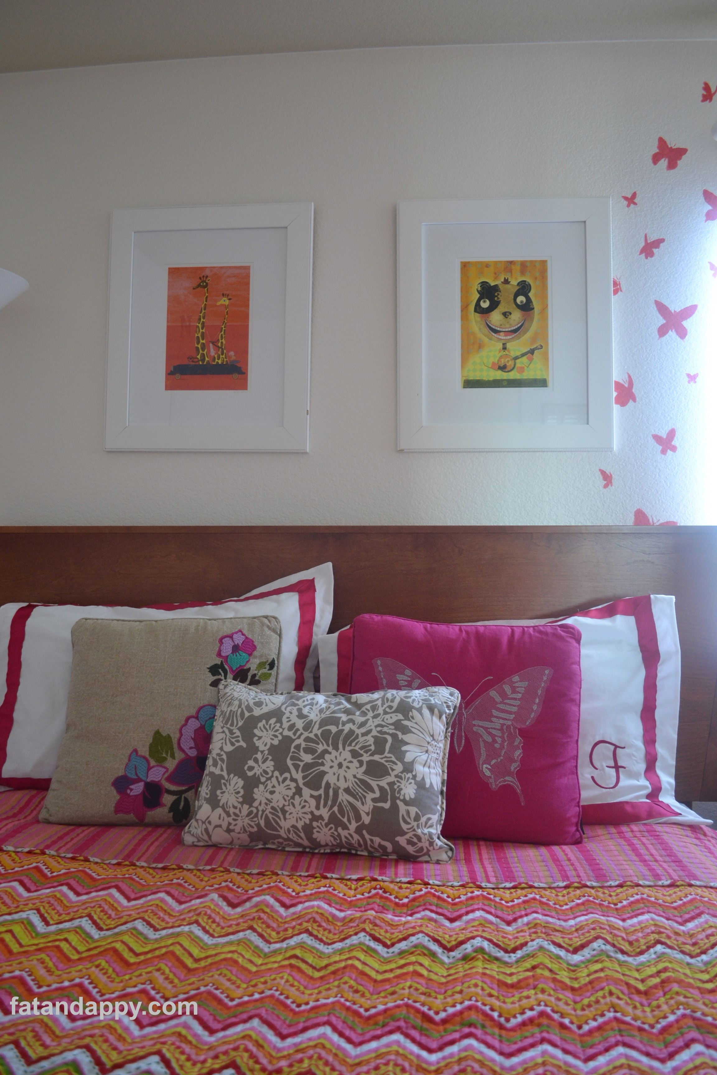 A closeup of the modern bed with pink pillows and artwork